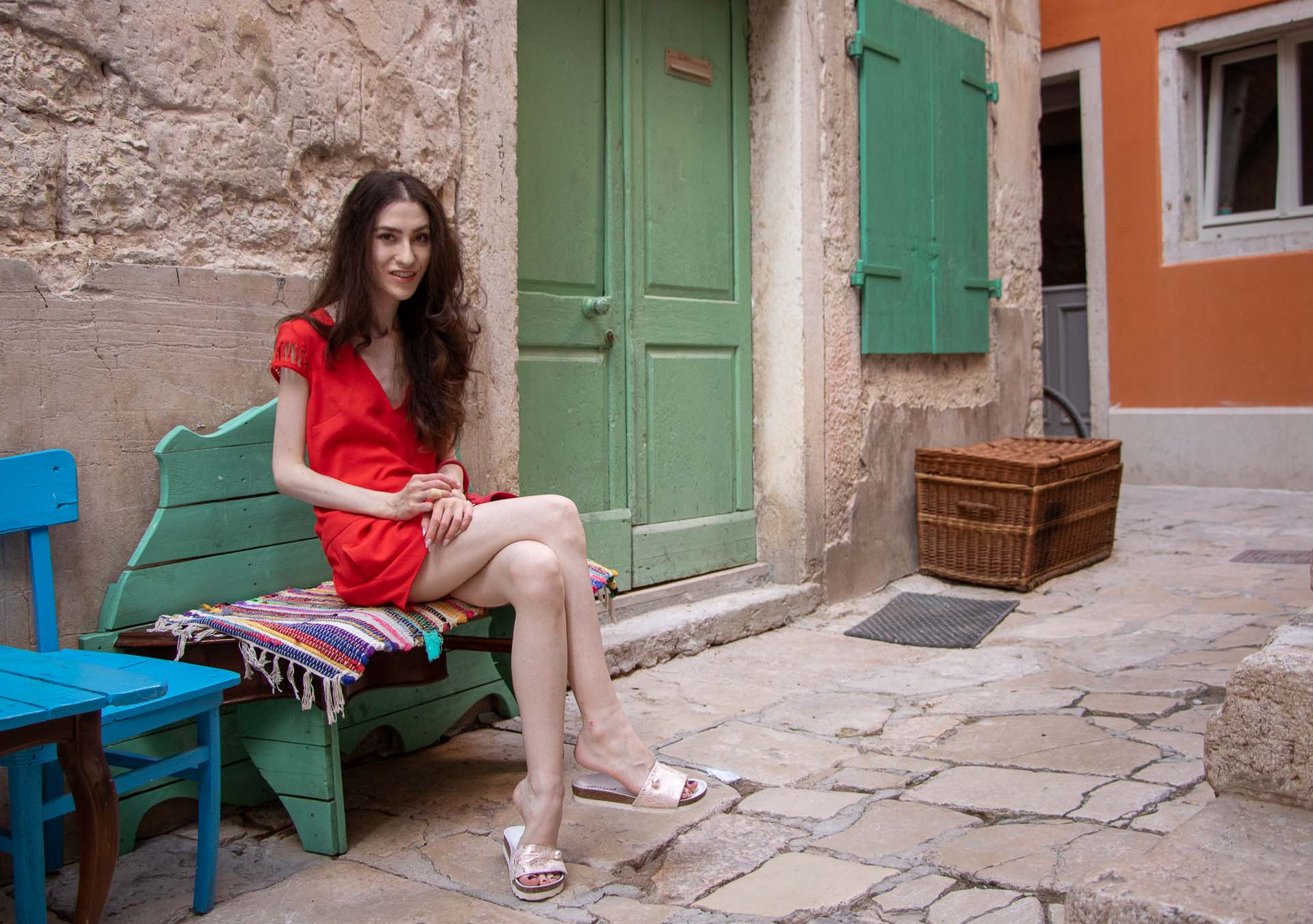 Fashion Blogger Veronika Lipar of Brunette from Wall Street wearing open back chic red romper, crystal-embellished lace luxe pool slides, pink top handle bag while sitting on the bench crossing legs in Rovinj