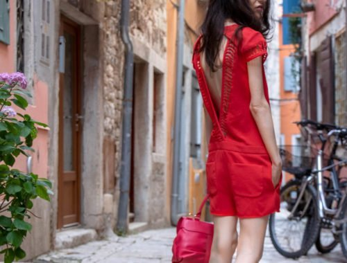 Fashion Blogger Veronika Lipar of Brunette from Wall Street wearing open back chic red romper, pink top handle bag while standing on the narrow picturesque street in Rovinj