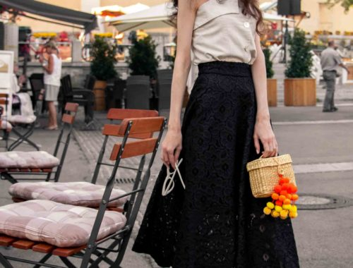 Fashion Blogger Veronika Lipar of Brunette from Wall Street dressed in beige linen crop top, black lace midi skirt, Stuart Weitzman high shine metallic nudist song sandals, Nannacay basket bag, cat eye sunglasses for shopping at the marketplace