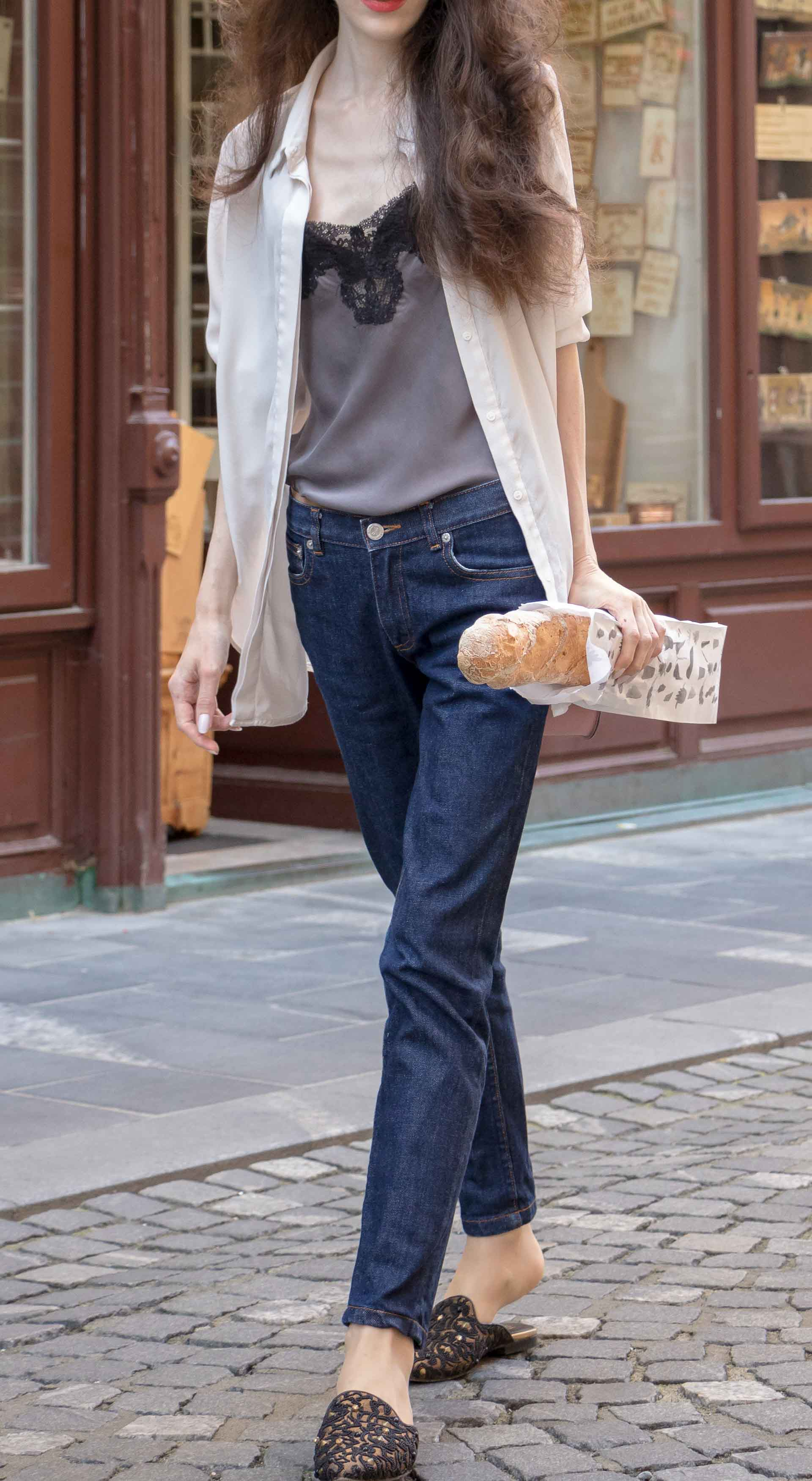 Fashion Blogger Veronika Lipar of Brunette from Wall Street dressed in white organza shirt with transparent back from Sandro Paris, grey silk slip top, A.P.C. dark denim jeans, mules, pink Furla shoulder bag, on her way from the bakery