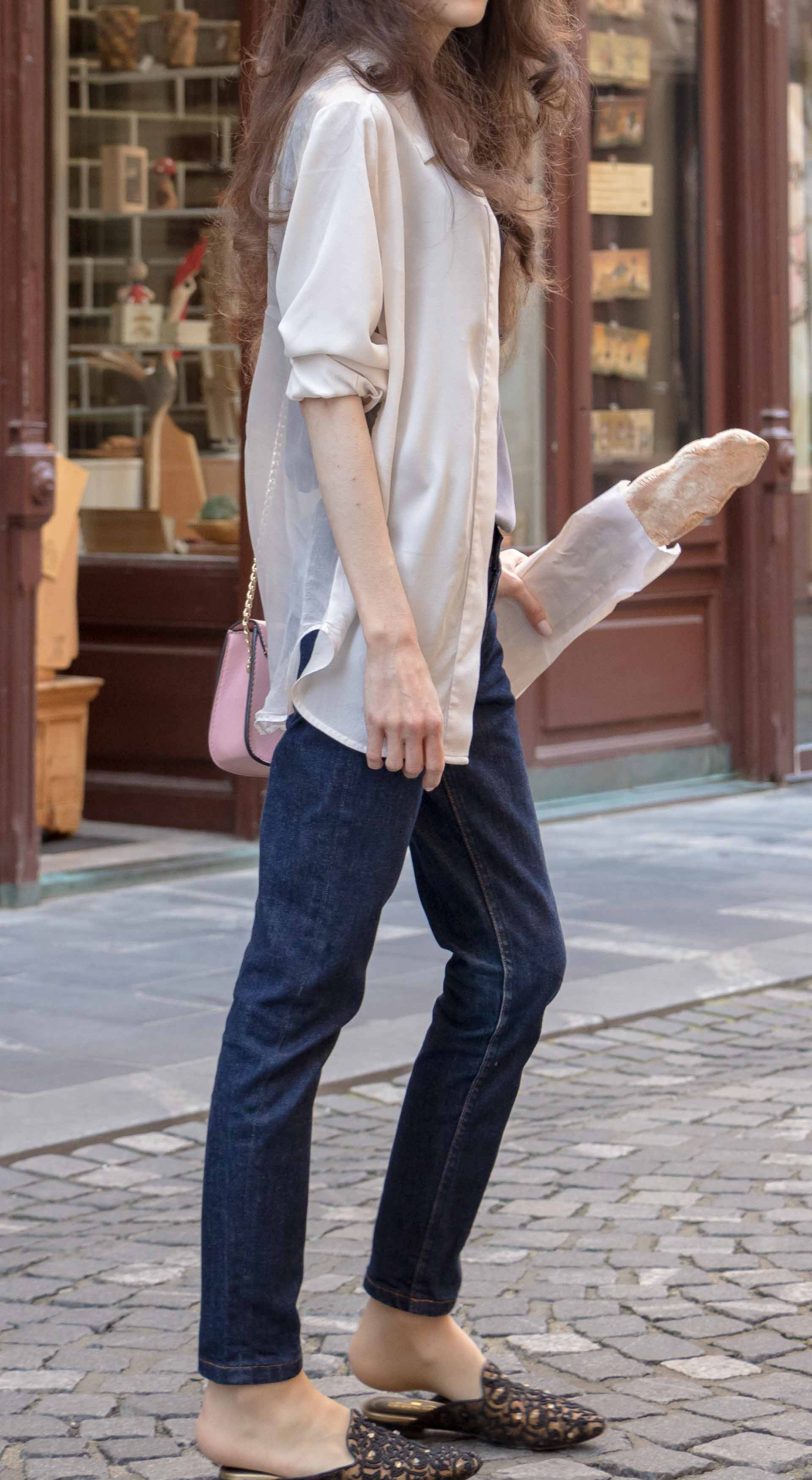 Fashion Blogger Veronika Lipar of Brunette from Wall Street wearing white transparent shirt with transparent back from Sandro Paris, grey silk slip top, A.P.C. dark denim jeans, mules, pink Furla shoulder bag, on her way from the bakery