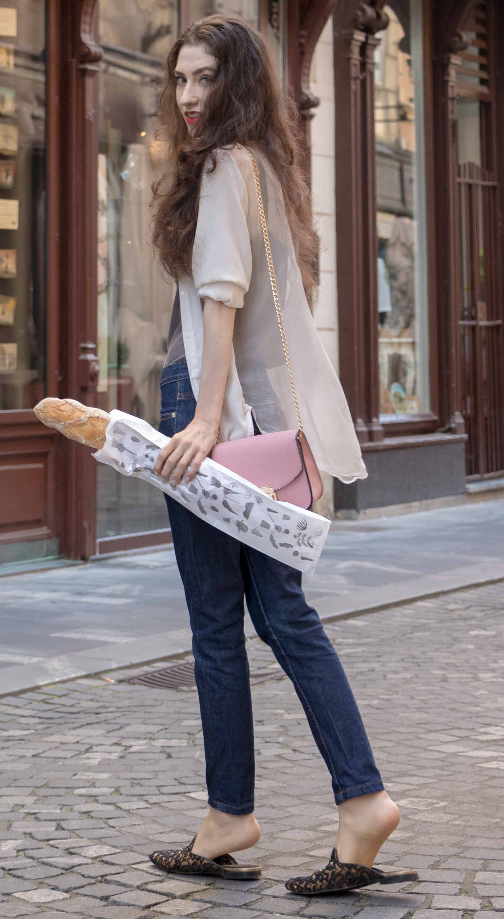 Fashion Blogger Veronika Lipar of Brunette from Wall Street wearing white sheer shirt with transparent back from Sandro Paris, grey silk slip top, A.P.C. dark denim jeans, mules, pink Furla shoulder bag, while holding a baguette walking on the street