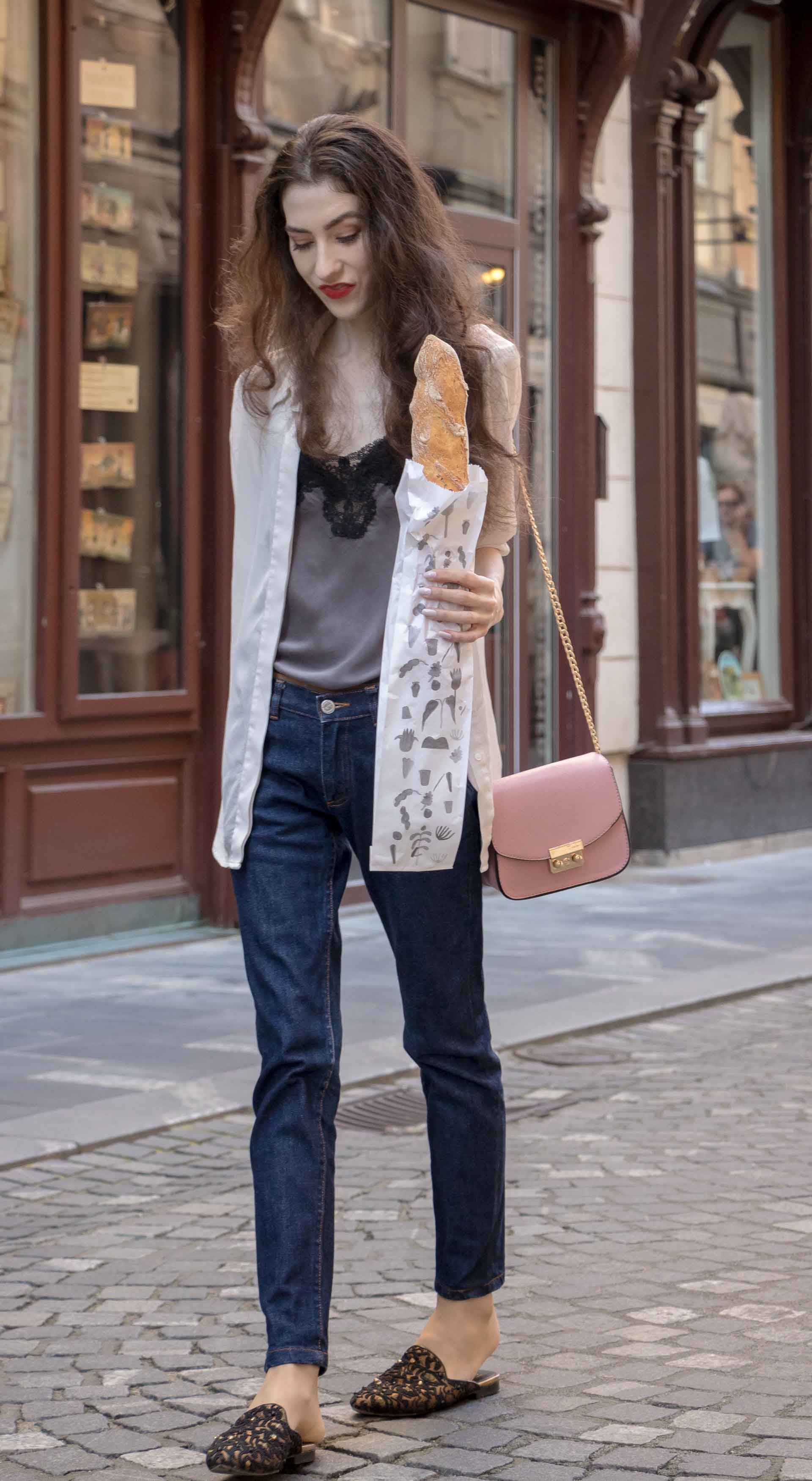 Fashion Blogger Veronika Lipar of Brunette from Wall Street wearing white organza shirt with transparent back from Sandro Paris, grey silk slip top, A.P.C. dark denim jeans, mules, pink Furla shoulder bag, on her way from the bakery