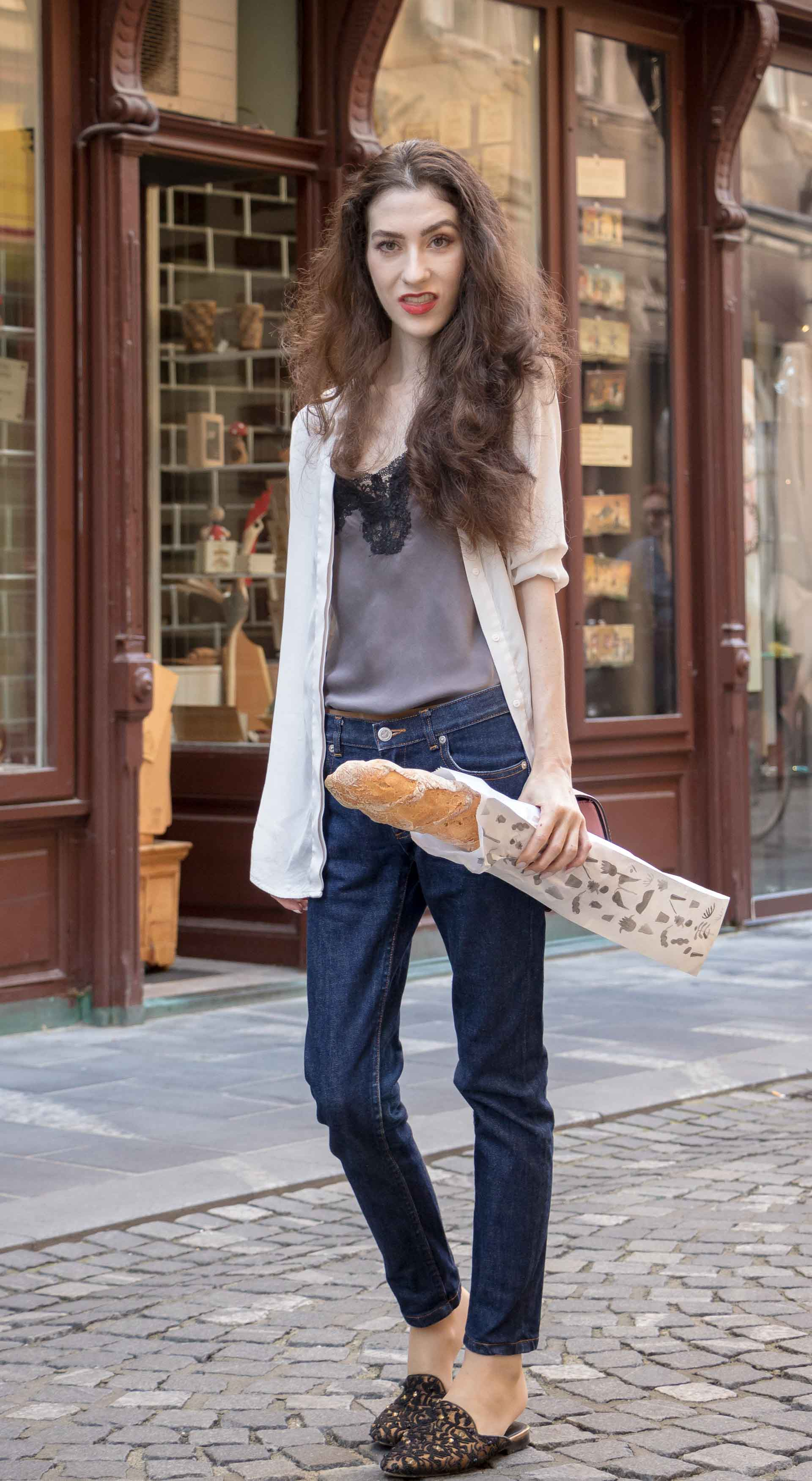 Fashion Blogger Veronika Lipar of Brunette from Wall Street dressed in white sheer shirt with transparent back from Sandro Paris, grey silk slip top, A.P.C. dark denim jeans, mules, pink Furla shoulder bag, on her way from the bakery