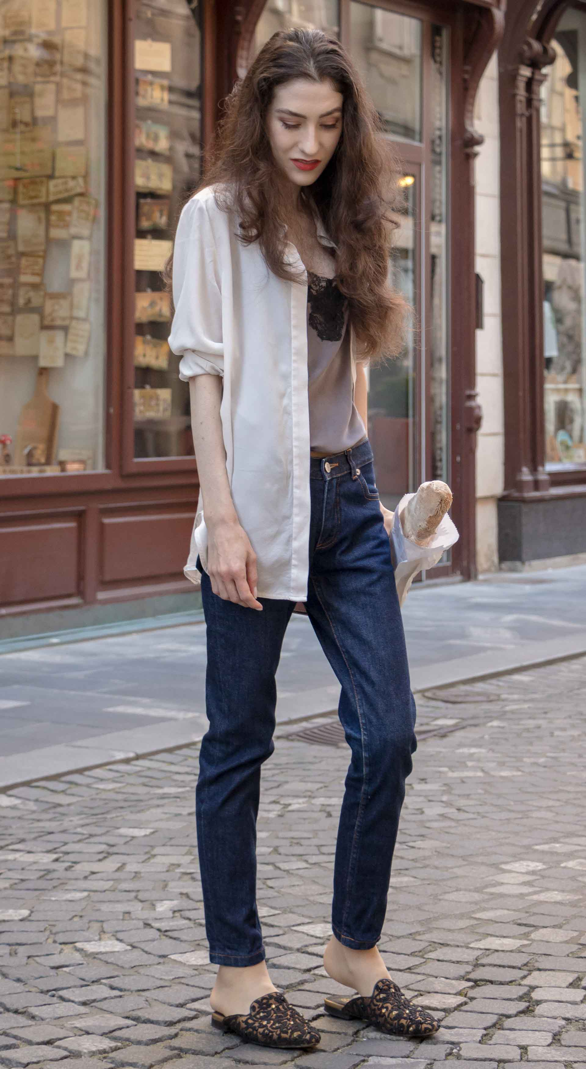 Fashion Blogger Veronika Lipar of Brunette from Wall Street wearing white transparent shirt with transparent back from Sandro Paris, grey silk slip top, A.P.C. dark denim jeans, mules, pink Furla shoulder bag, while holding a baguette on the street