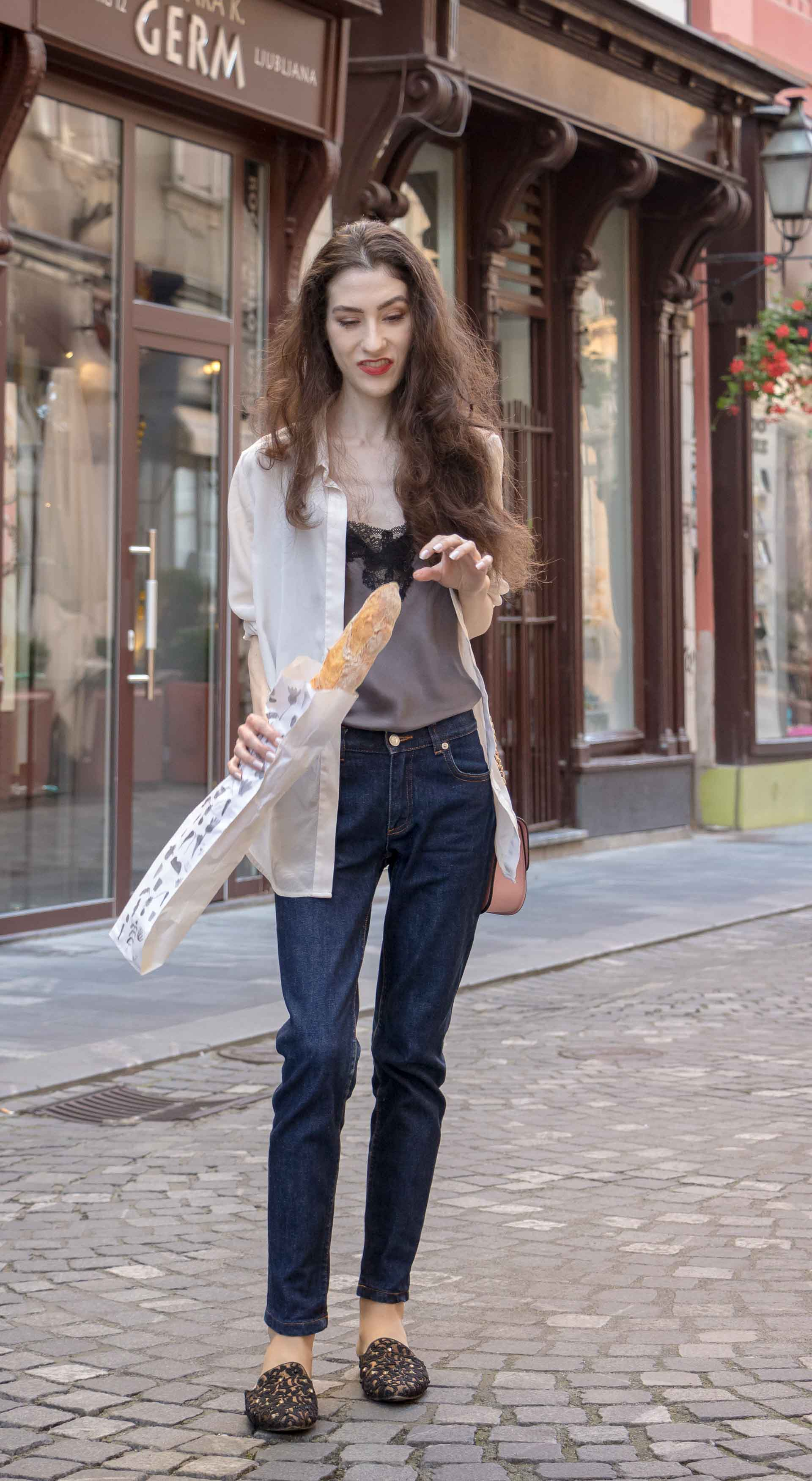 Fashion Blogger Veronika Lipar of Brunette from Wall Street dressed in white organza shirt with transparent back from Sandro Paris, grey silk slip top, A.P.C. dark denim jeans, mules, pink Furla shoulder bag, while holding a baguette on the street