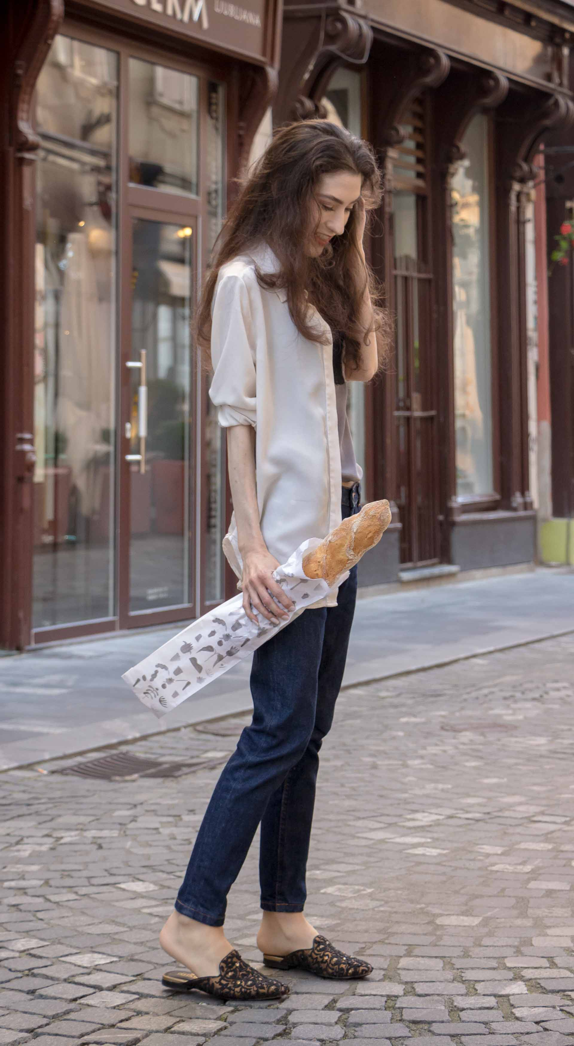 Fashion Blogger Veronika Lipar of Brunette from Wall Street dressed in white sheer shirt with transparent back from Sandro Paris, grey silk slip top, A.P.C. dark denim jeans, mules, pink Furla shoulder bag, while holding a baguette on the street