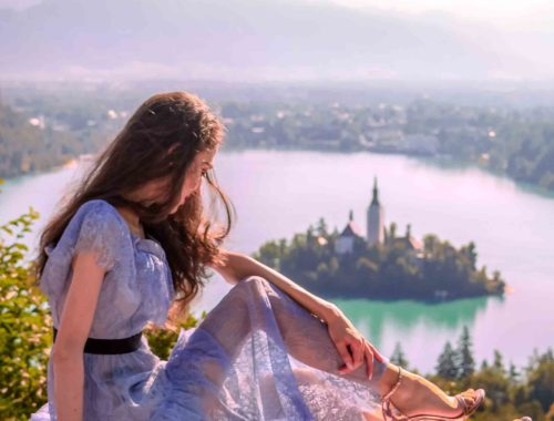 Beautiful Slovenian Fashion Blogger Veronika Lipar of Brunette from Wall dressed in Self-Portrait blue lace midi dress, Stuart Weitzman high shine metallic nudist song sandals, Nannacay basket bag while sitting on the picnic blanket above the lake Bled