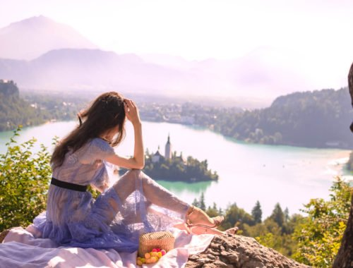 Beautiful Slovenian Fashion Blogger Veronika Lipar of Brunette from Wall wearing Self-Portrait blue lace midi dress, Stuart Weitzman high shine metallic nudist song sandals, Nannacay basket bag while sitting on the blanket looking down to the lake Bled