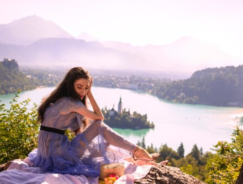 Beautiful Slovenian Fashion Blogger Veronika Lipar of Brunette from Wall wearing Self-Portrait blue lace midi dress, Stuart Weitzman high shine metallic nudist song sandals, Nannacay basket bag while having a romantic date in Slovenian Alps