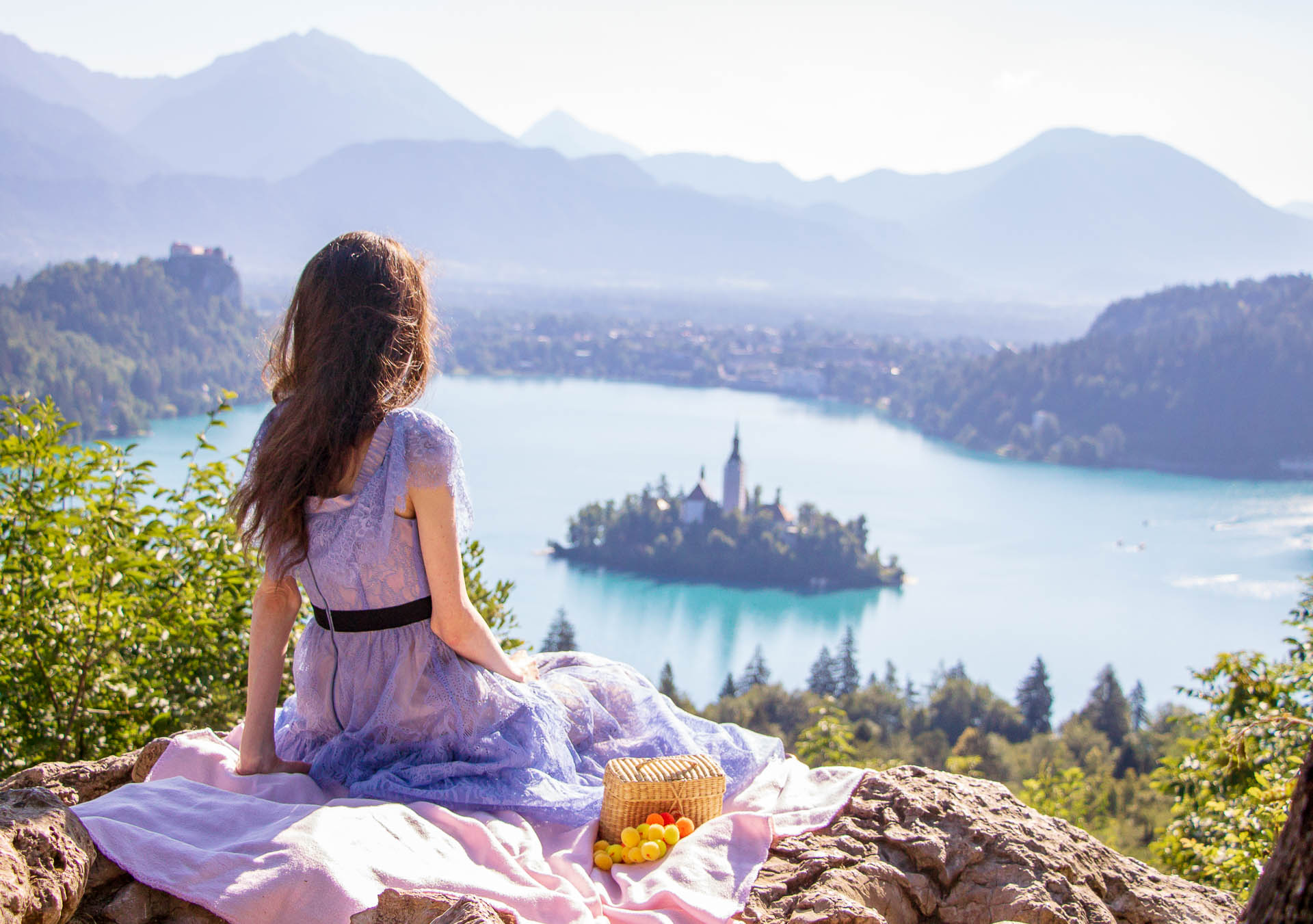 Beautiful Slovenian Fashion Blogger Veronika Lipar of Brunette from Wall dressed in Self-Portrait blue lace midi dress, Stuart Weitzman high shine metallic nudist song sandals, Nannacay basket bag while sitting on the blanket looking down to the lake Bled
