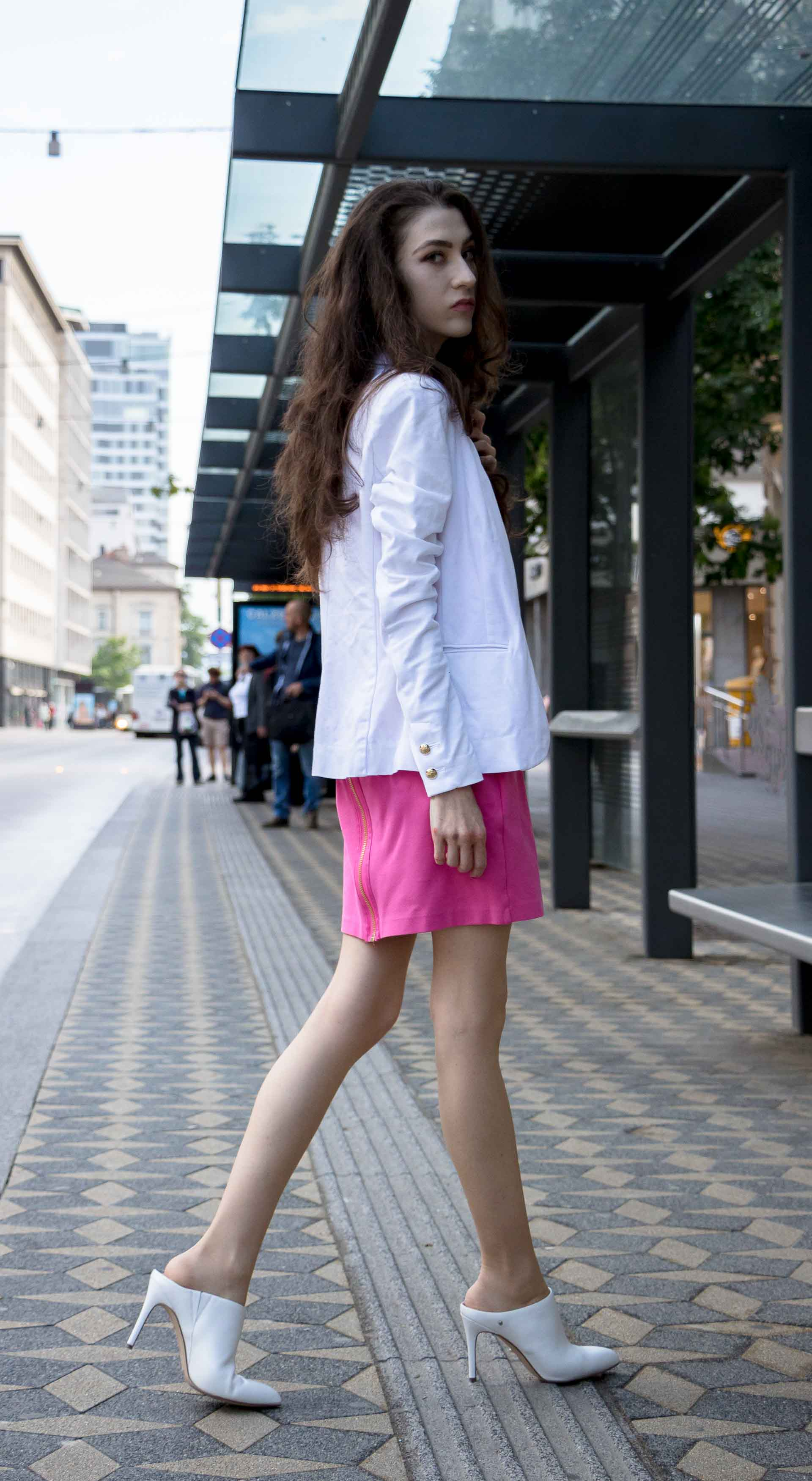 Fashion Blogger Veronika Lipar of Brunette from Wall Street wearing summer business casual outfit, white high heel close toe mules, pink tailored short dress, white blazer, pink top handle bag rushing to work