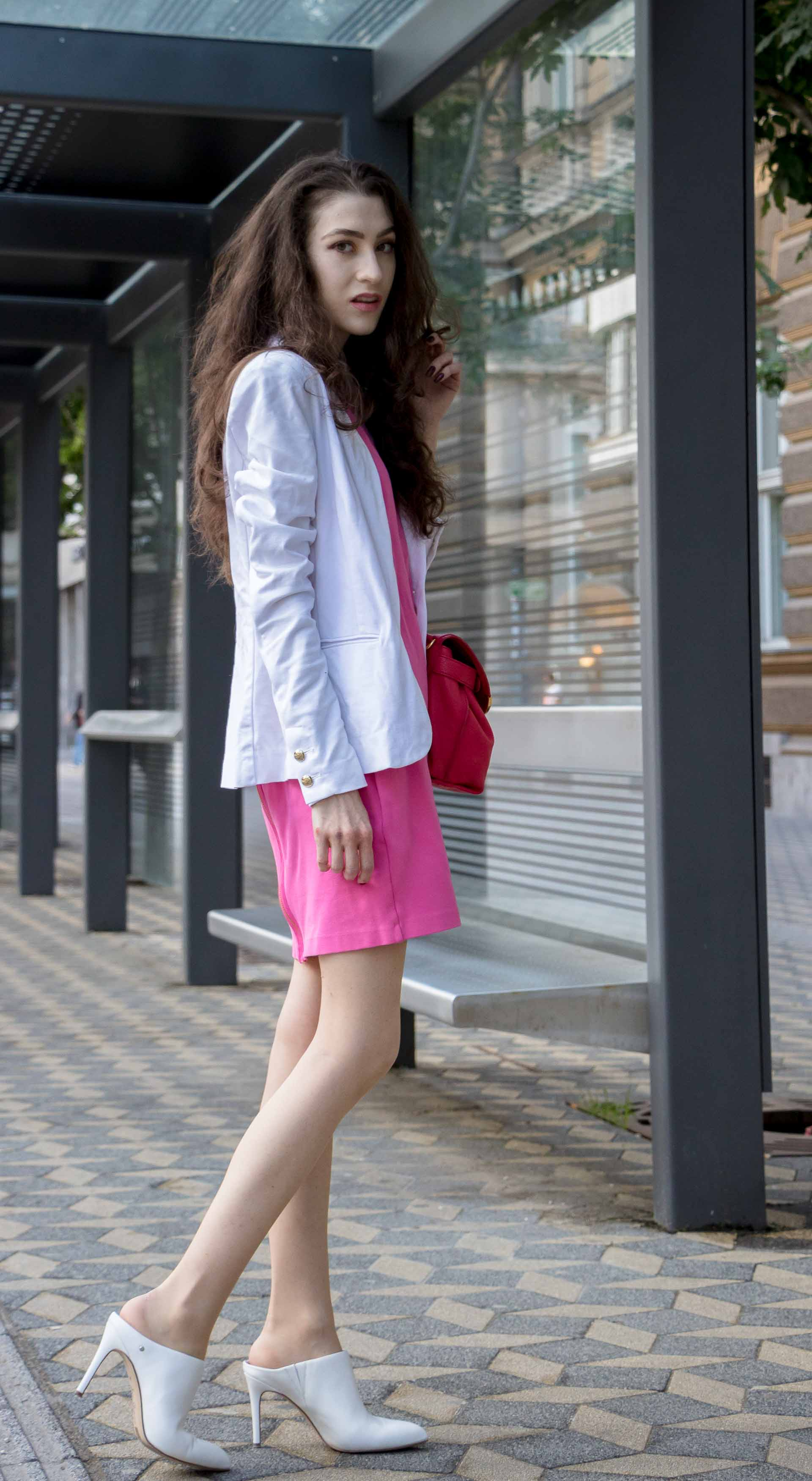 Fashion Blogger Veronika Lipar of Brunette from Wall Street wearing summer business casual outfit, white high heel close toe mules, pink tailored short dress, white blazer, pink top handle bag on her way to work