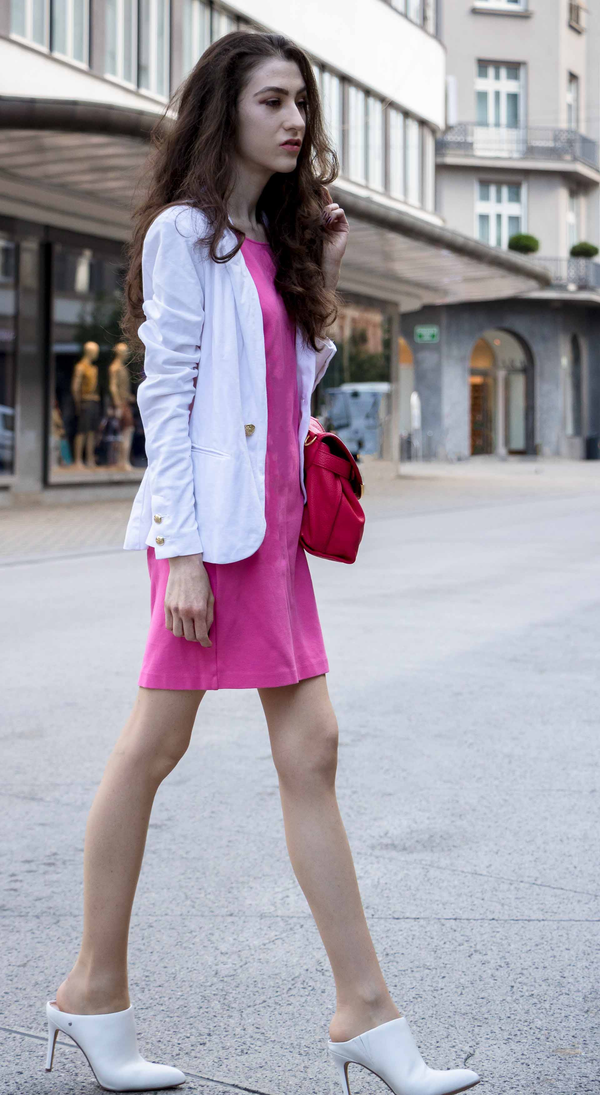 Fashion Blogger Veronika Lipar of Brunette from Wall Street dressed in summer business casual outfit, white high heel close toe mules, pink tailored short dress, white blazer, pink top handle bag crossing the street in Ljubljana