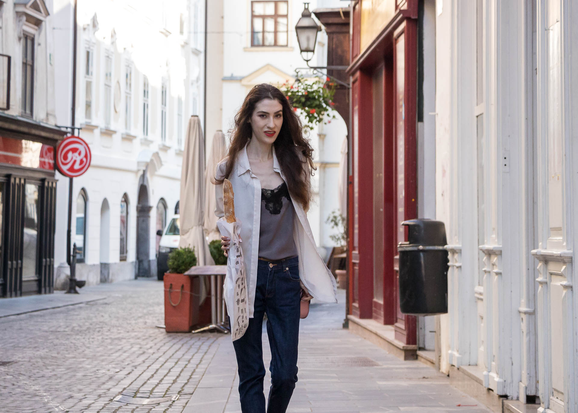 Fashion Blogger Veronika Lipar of Brunette from Wall Street wearing white sheer shirt with transparent back from Sandro Paris, grey silk slip top, A.P.C. dark denim jeans, mules, pink Furla shoulder bag, while holding a baguette on the street