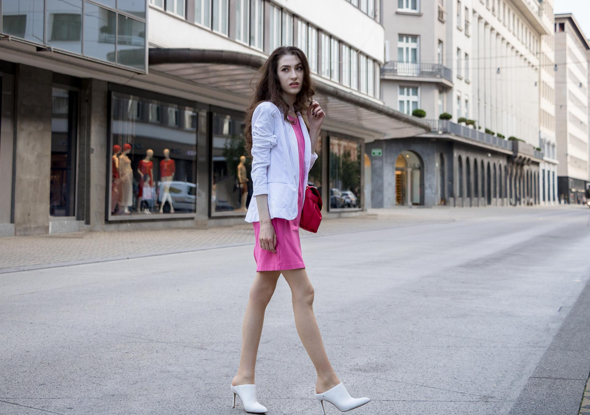 Fashion Blogger Veronika Lipar of Brunette from Wall Street wearing summer business casual outfit, white high heel close toe mules, pink tailored short dress, white blazer, pink top handle bag crossing the street in Ljubljana