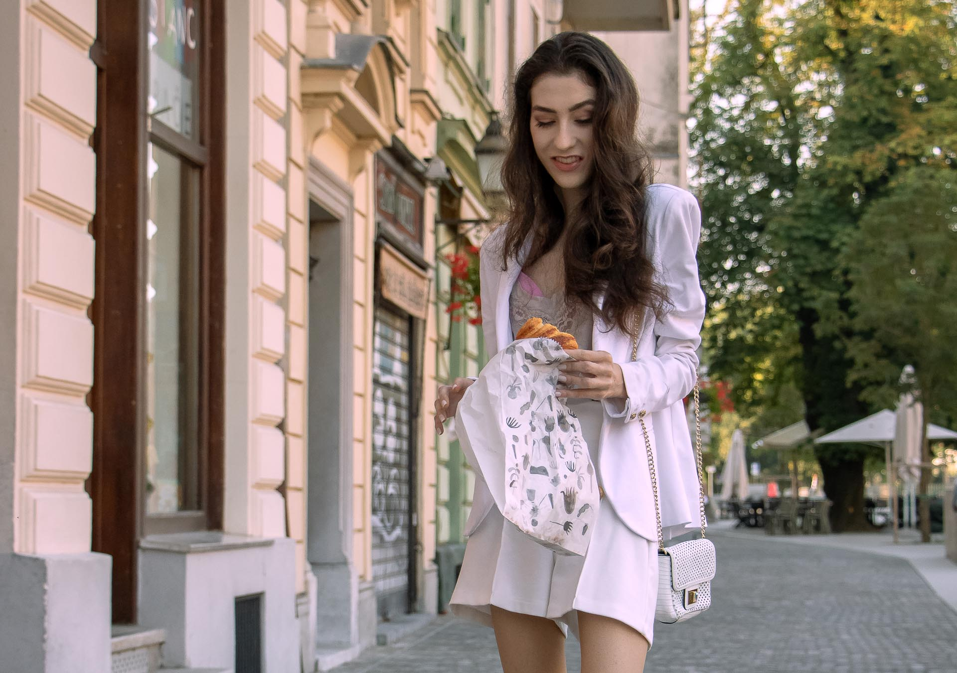Beautiful Slovenian Fashion Blogger Veronika Lipar of Brunette from Wall wearing all in white suit, white blazer, white tailored shorts, Stuart Weitzman high shine metallic nudist song sandals, shoulder bag with a paper bag on the street in the morning after party