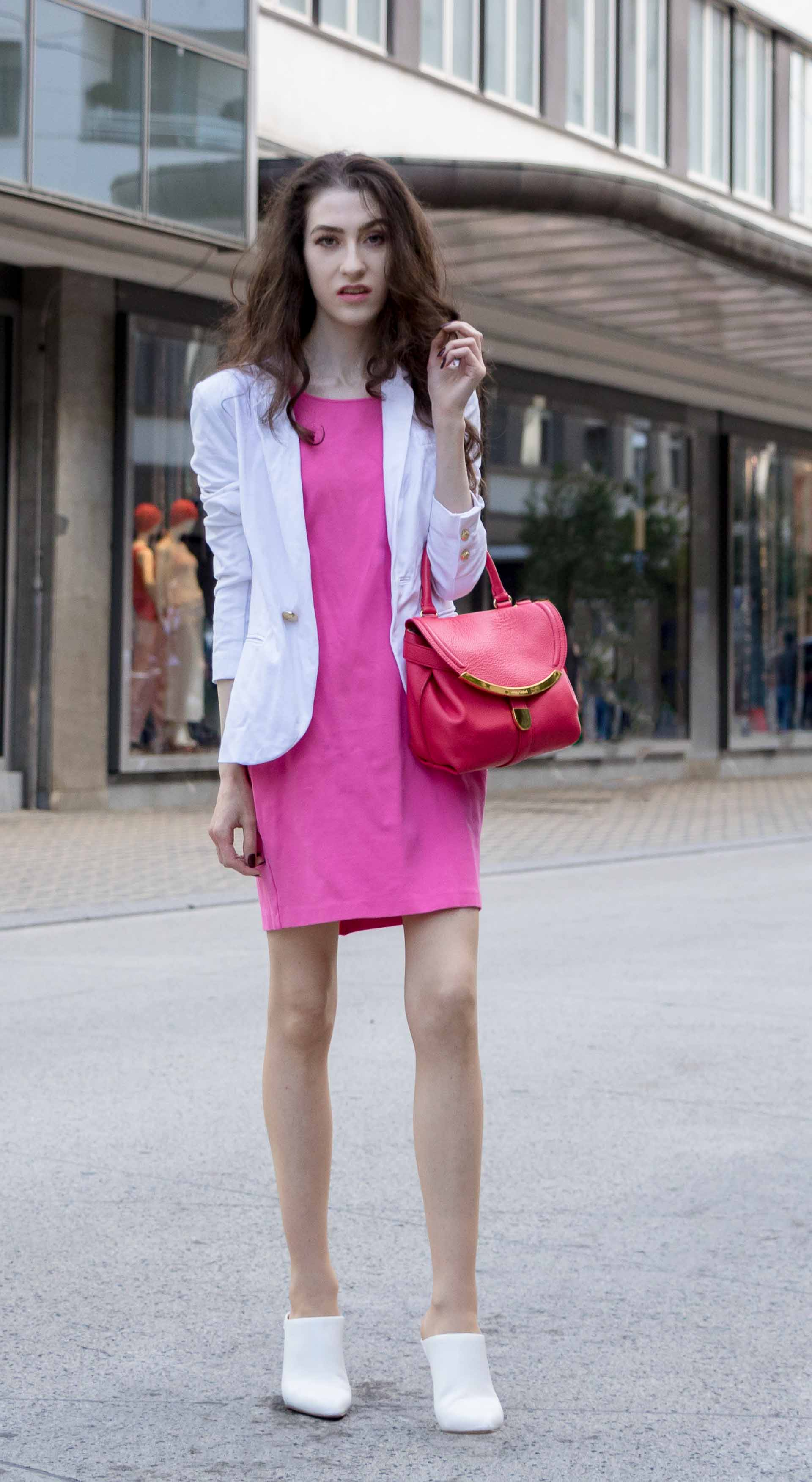 Fashion Blogger Veronika Lipar of Brunette from Wall Street dressed in summer business casual outfit, white high heel close toe mules, pink tailored short dress, white blazer, pink top handle bag rushing to work