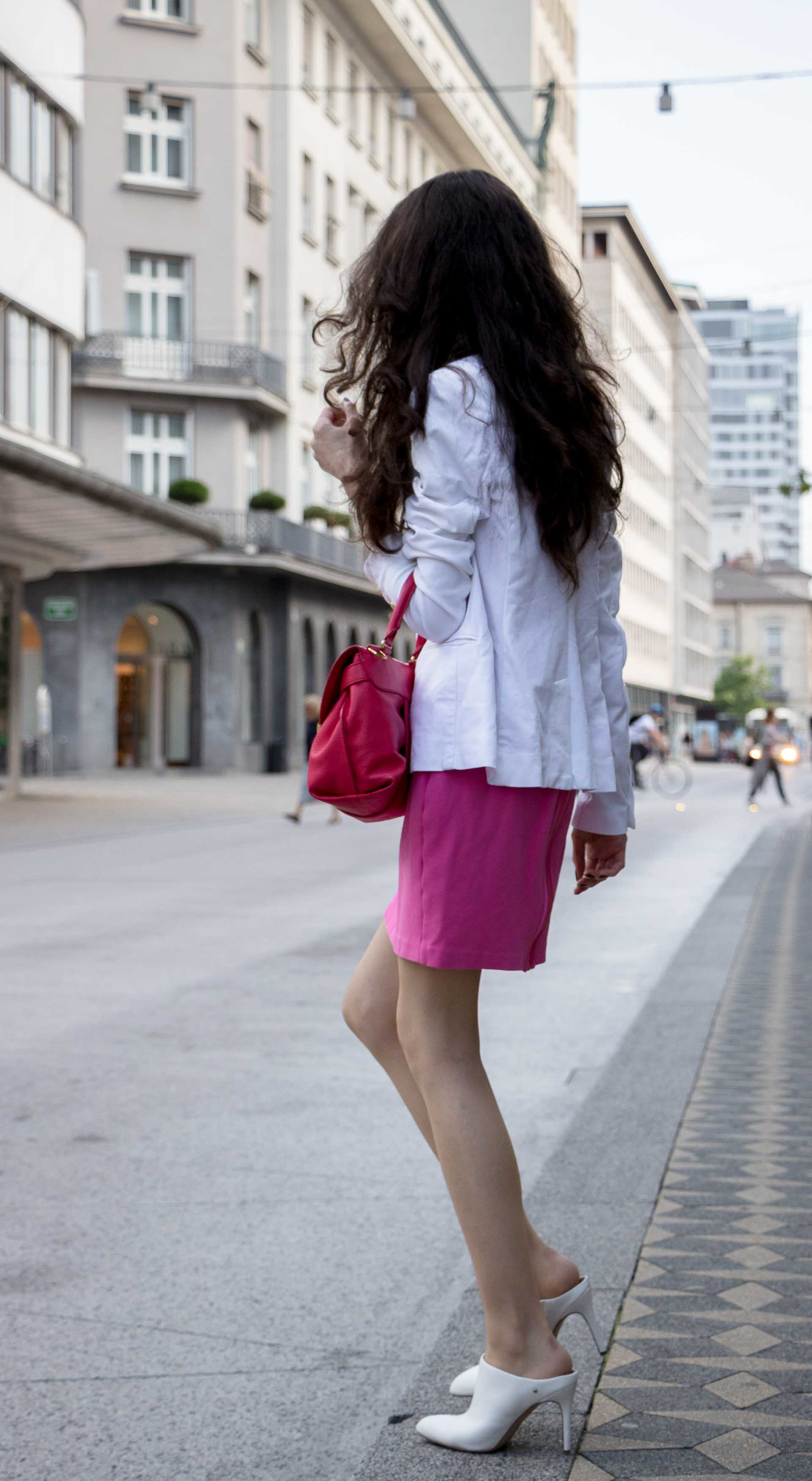 Fashion Blogger Veronika Lipar of Brunette from Wall Street dressed in summer business casual outfit, white high heel close toe mules, pink tailored short dress, white blazer, pink top handle bag running to work