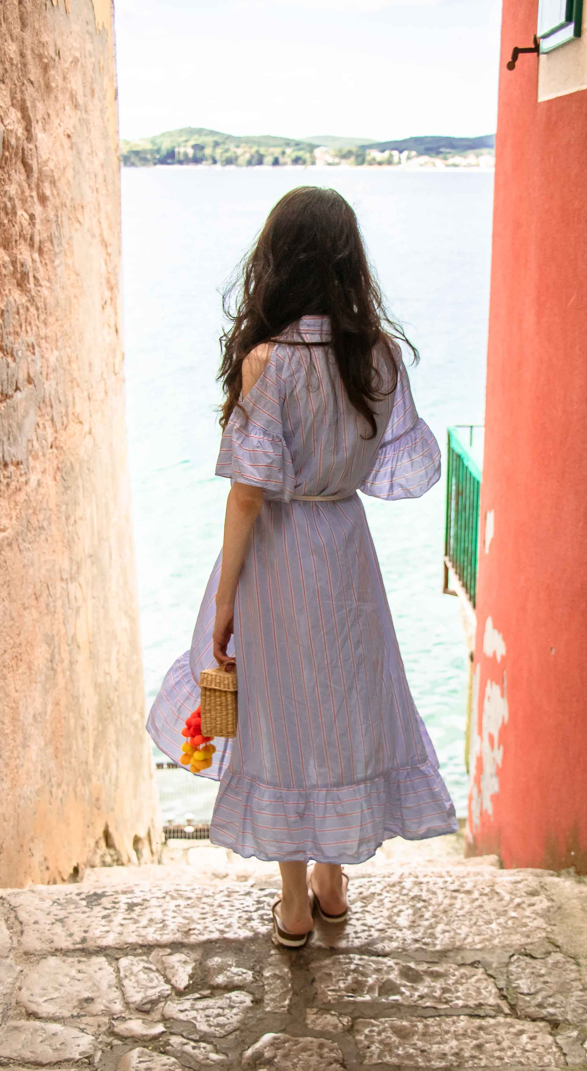 Fashion Blogger Veronika Lipar of Brunette from Wall Street dressed in Storets cold shoulder striped ruffled summer dress, blush lace pool luxe slides