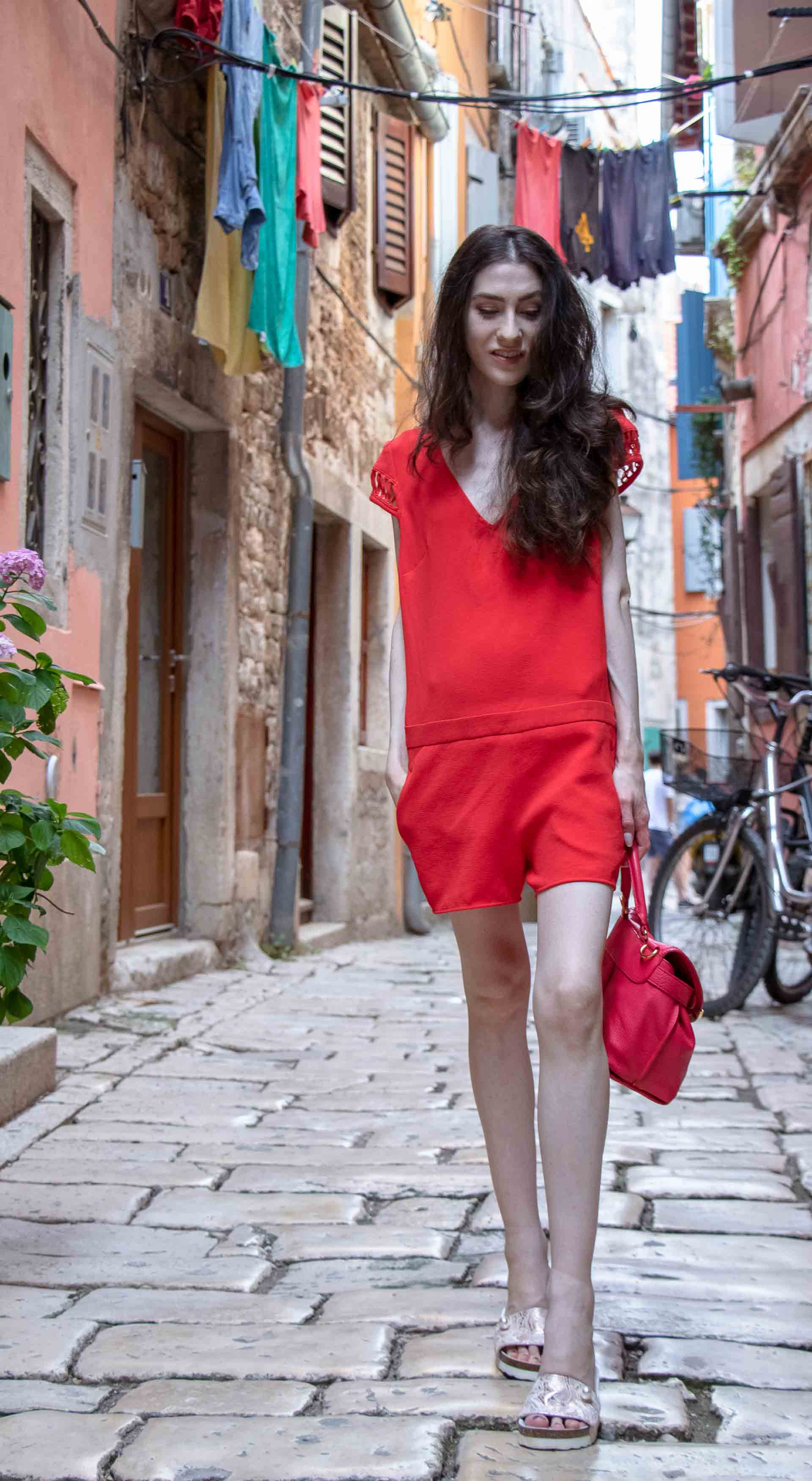 Fashion Blogger Veronika Lipar of Brunette from Wall Street dressed in open back chic red romper, crystal-embellished lace luxe pool slides, pink top handle bag while walking down the narrow picturesque street in Rovinj
