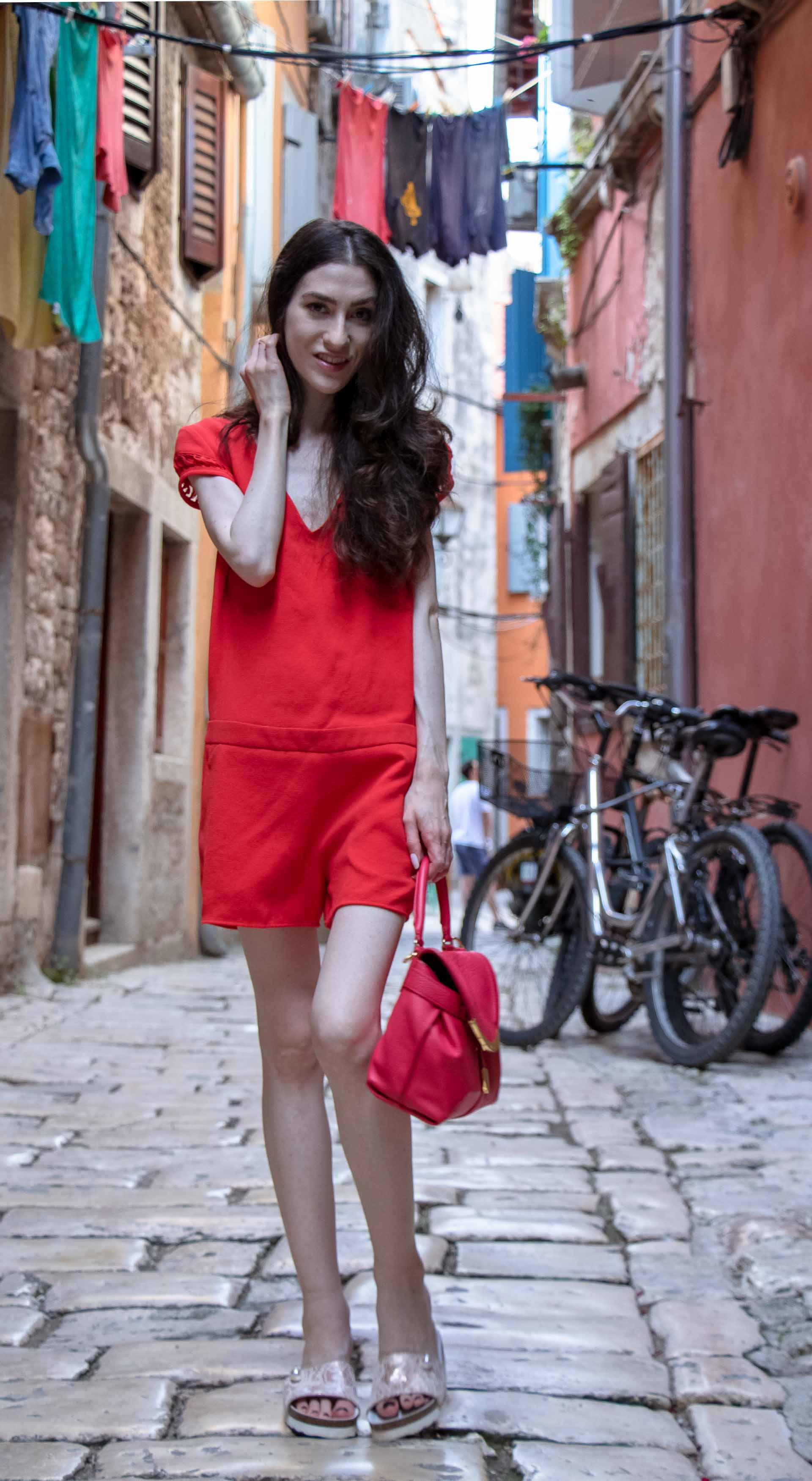 Fashion Blogger Veronika Lipar of Brunette from Wall Street wearing open back chic red romper, crystal-embellished lace luxe pool slides, pink top handle bag while standing on the narrow picturesque street in Rovinj