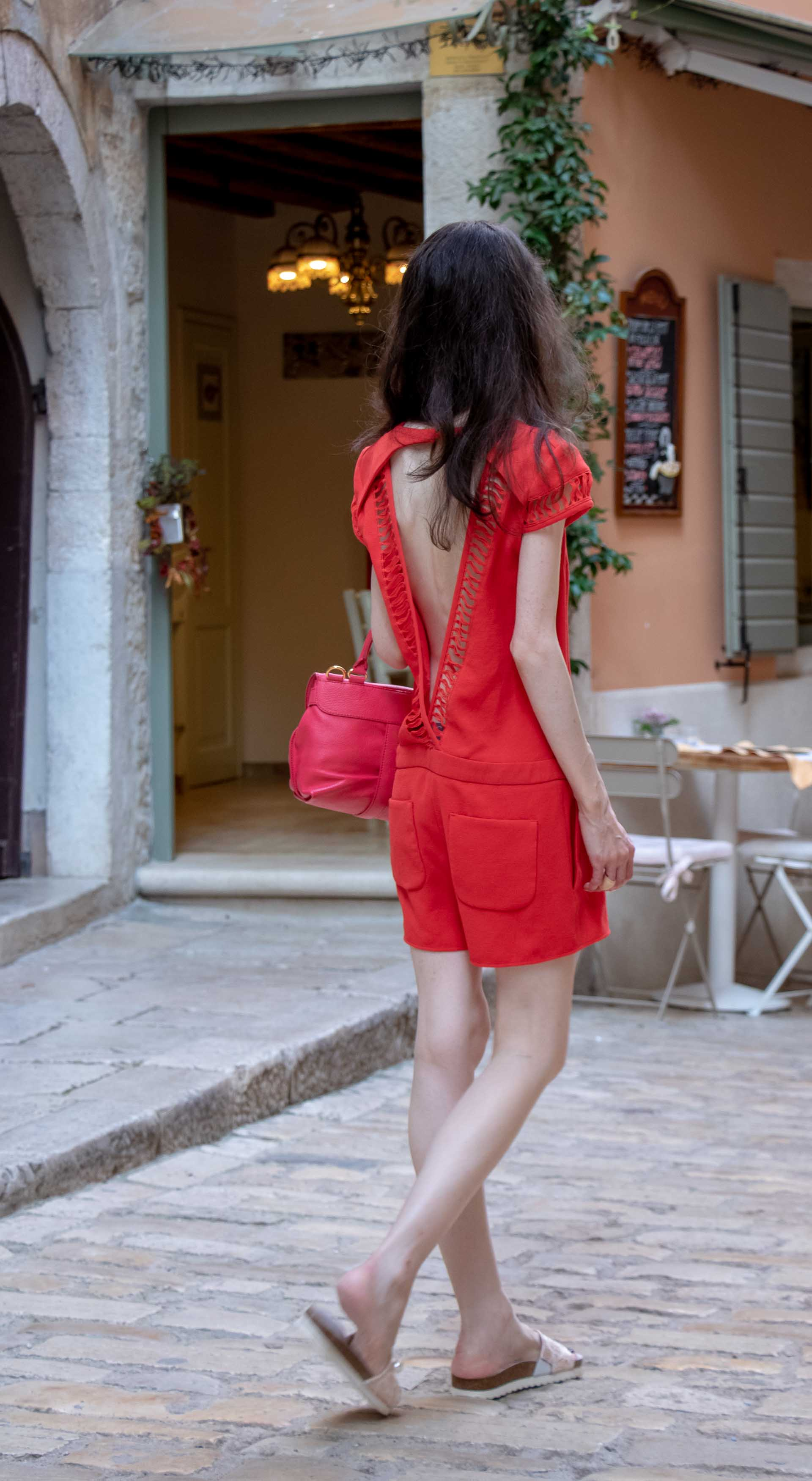 Fashion Blogger Veronika Lipar of Brunette from Wall Street wearing open back chic red romper, crystal-embellished lace luxe pool slides, pink top handle bag while walking down the narrow picturesque street in Rovinj