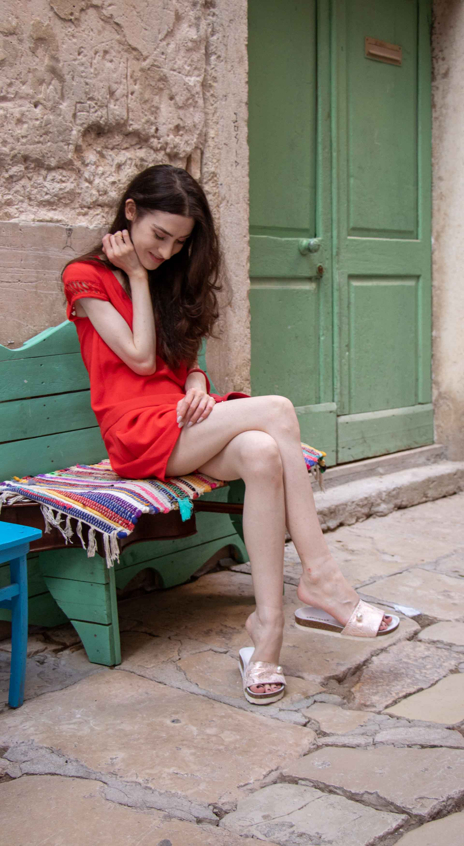 Fashion Blogger Veronika Lipar of Brunette from Wall Street wearing open back chic red romper, crystal-embellished lace luxe pool slides, pink top handle bag while sitting on the bench in Rovinj