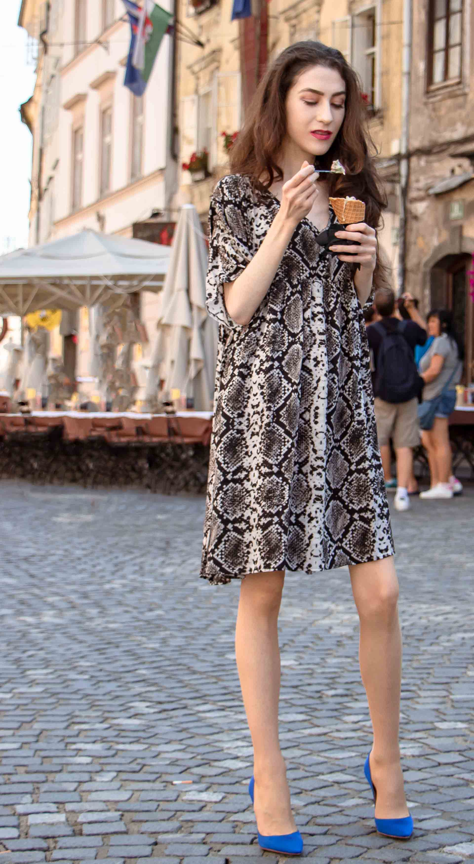 Beautiful Slovenian Fashion Blogger Veronika Lipar of Brunette from Wall wearing flowing short snake print dress from Zara, blue Gianvito Rossi satin pumps, eating ice cream on the street