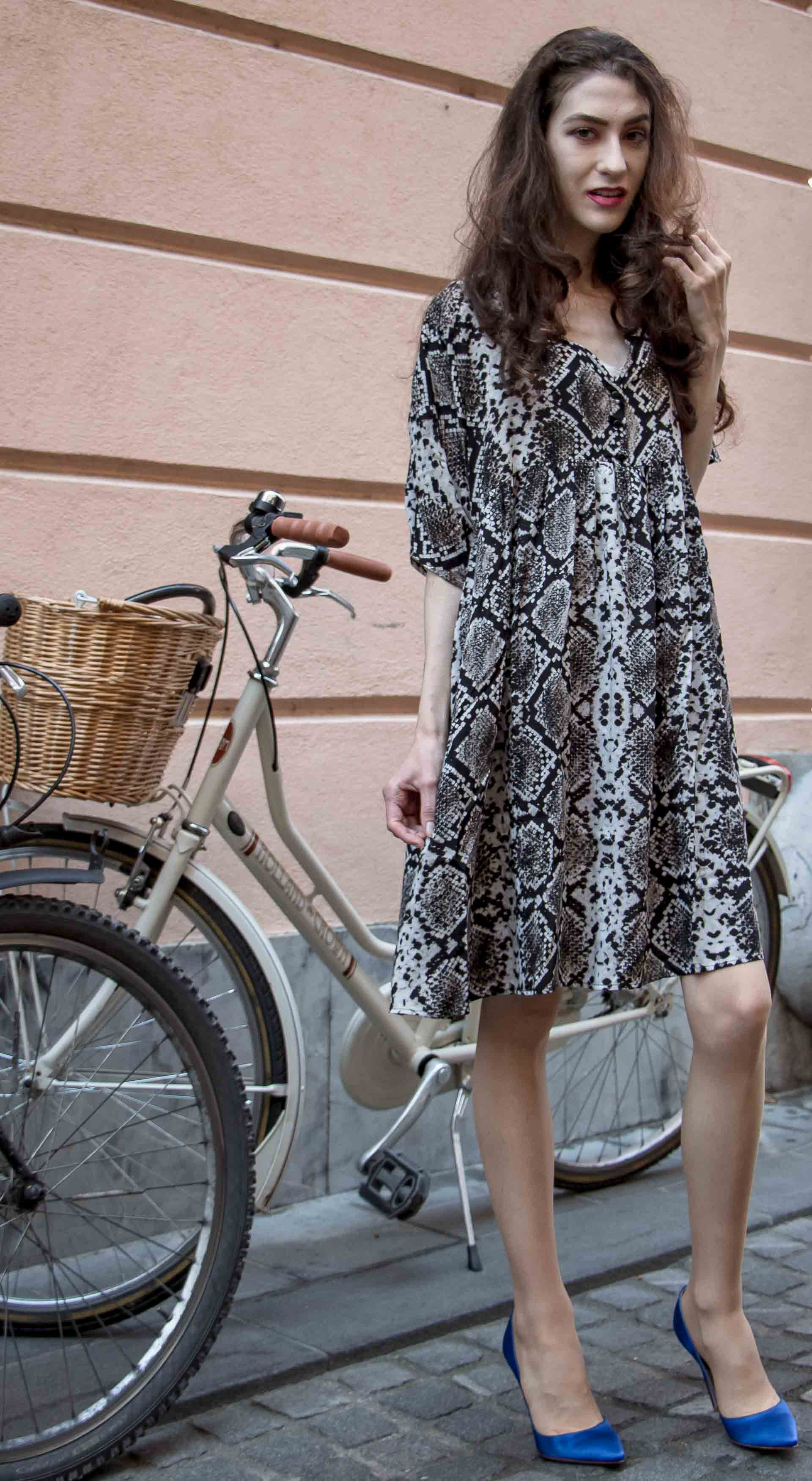 Beautiful Slovenian Fashion Blogger Veronika Lipar of Brunette from Wall dressed in flowing short snake print dress from Zara, blue Gianvito Rossi satin pumps, standing by the bicycle on the street in Ljubljana
