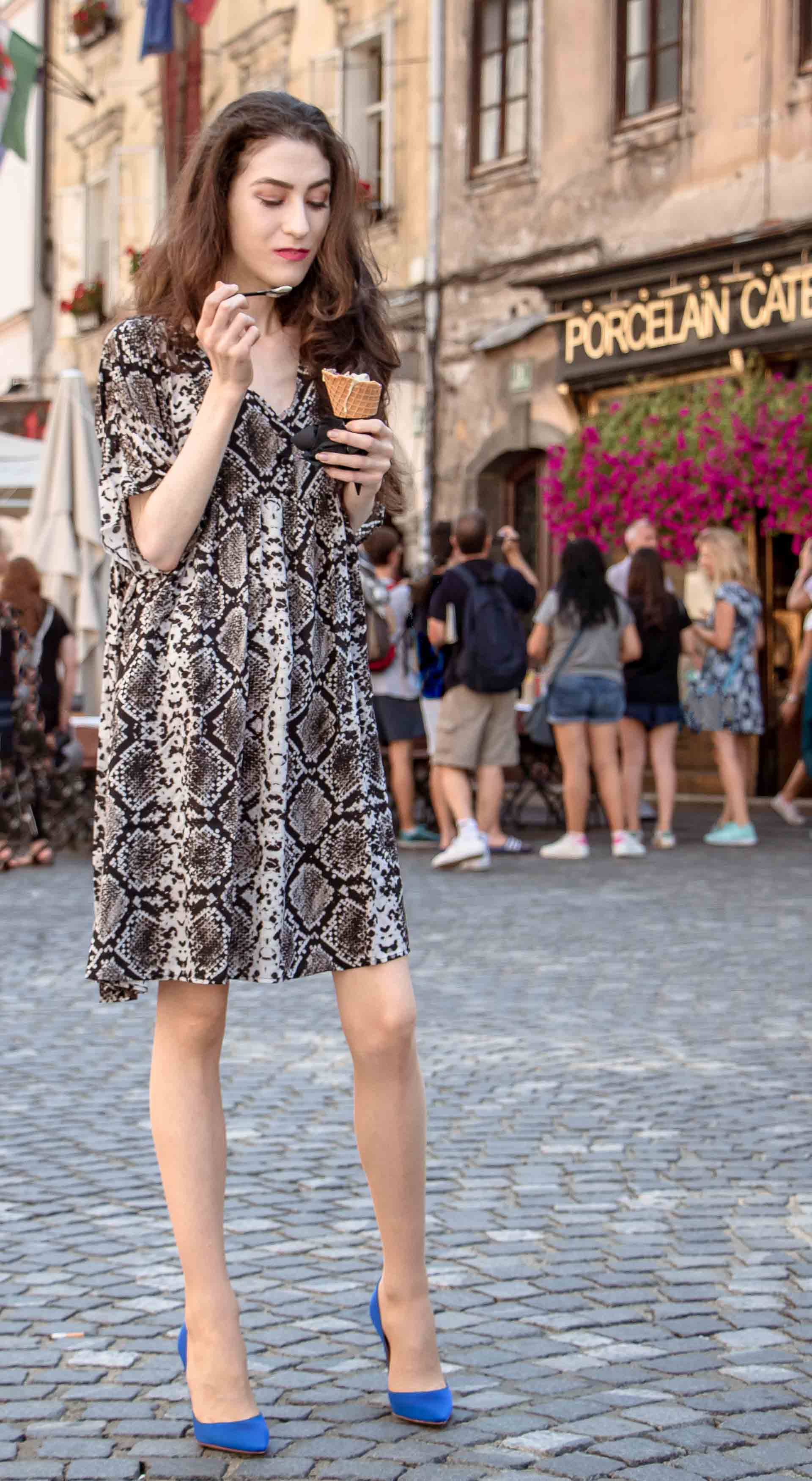 Beautiful Slovenian Fashion Blogger Veronika Lipar of Brunette from Wall dressed in flowing short snake print dress from Zara, blue Gianvito Rossi satin pumps, eating ice cream on the street