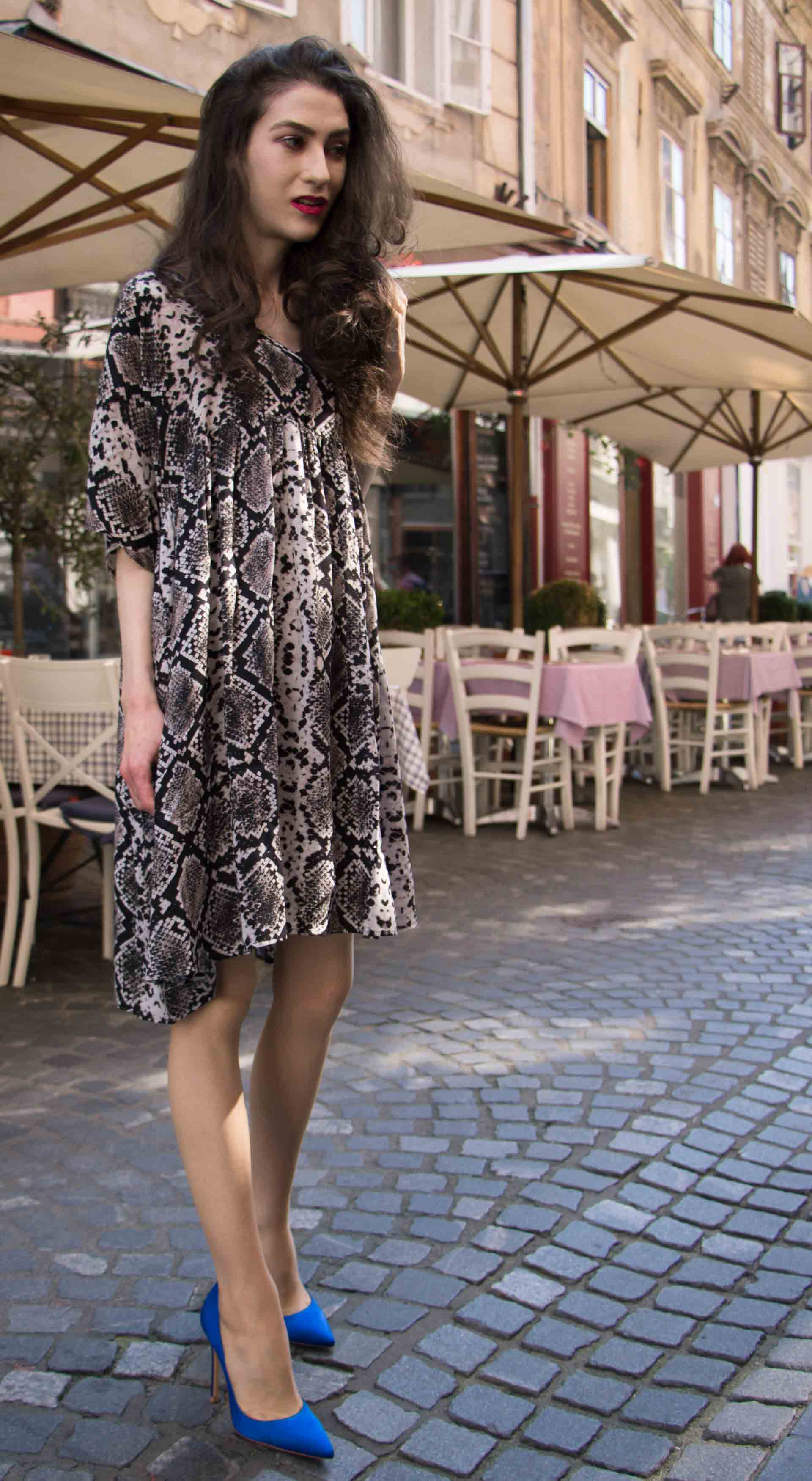 Beautiful Slovenian Fashion Blogger Veronika Lipar of Brunette from Wall dressed in flowing short snake print dress from Zara, blue Gianvito Rossi satin pumps, standing by the restaurant tables on the street