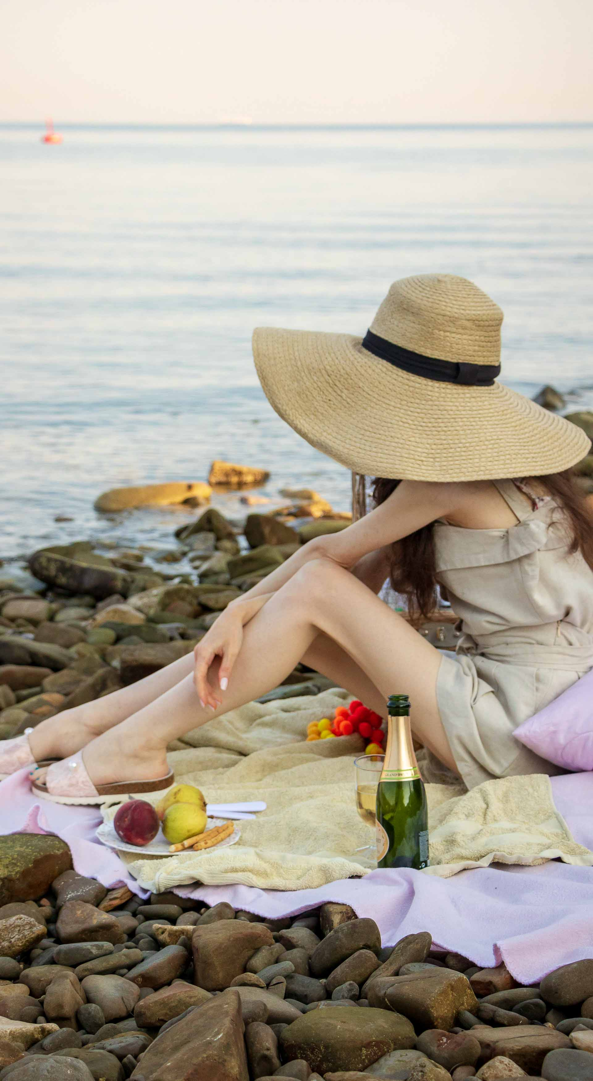 Slovenian Fashion Blogger Veronika Lipar of Brunette from Wall wearing beige linen crop top, paper bag linen shorts, luxe pool slides, large straw hat, Nannacay basket bag while sitting on a picnic blanket and staring at the sea