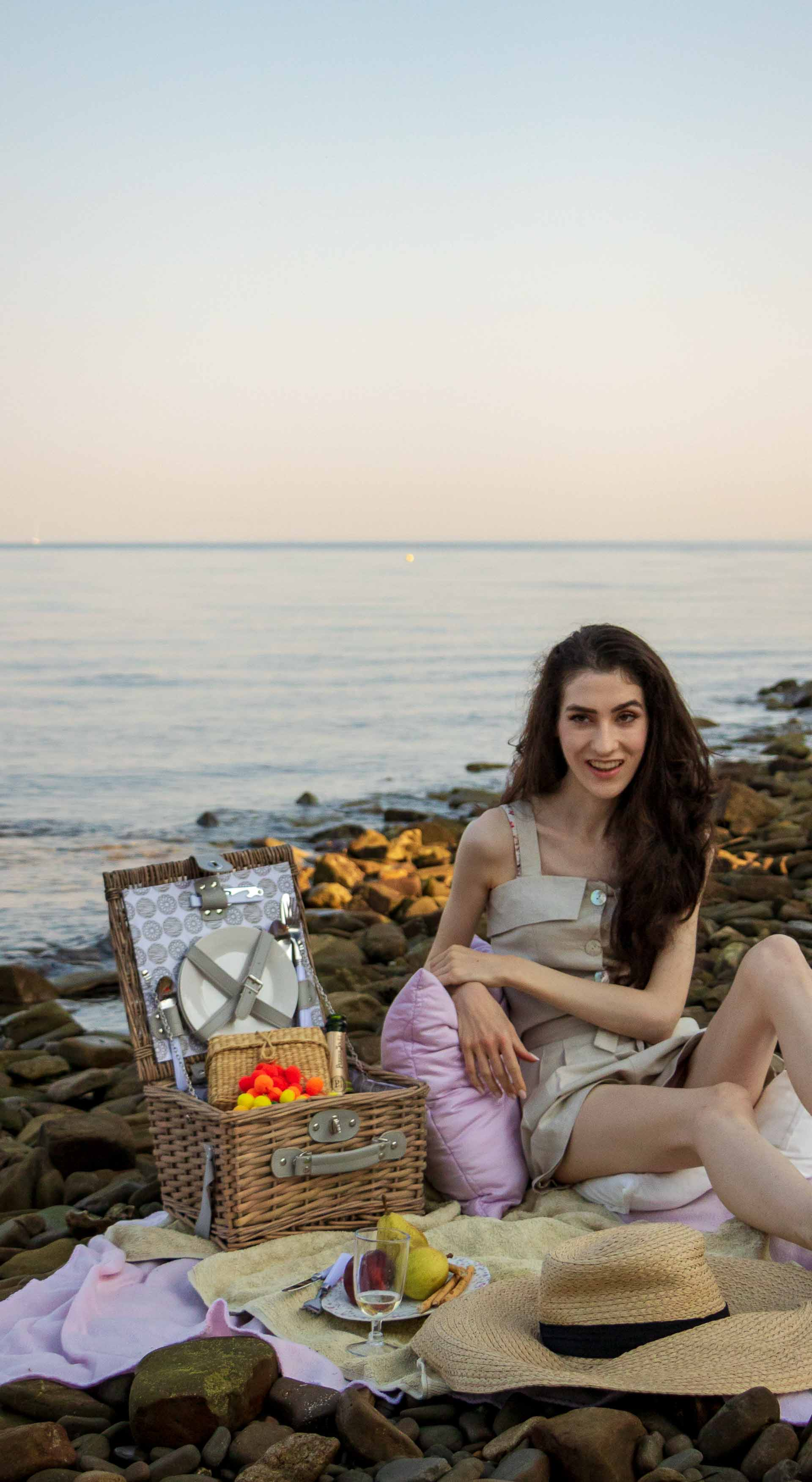 Slovenian Fashion Blogger Veronika Lipar of Brunette from Wall wearing beige linen crop top, paper bag linen shorts, luxe pool slides, large straw hat, Nannacay basket bag while sitting on a picnic blanket, having picnic on the beach