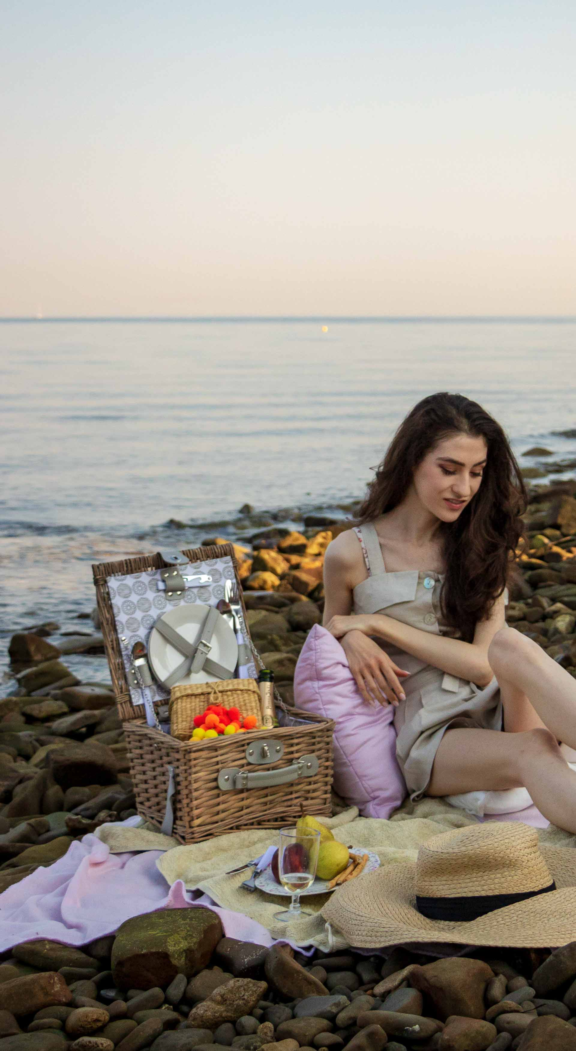 Slovenian Fashion Blogger Veronika Lipar of Brunette from Wall wearing beige linen crop top, paper bag linen shorts, luxe pool slides, large straw hat, Nannacay basket bag while sitting on a picnic blanket, having beach picnic