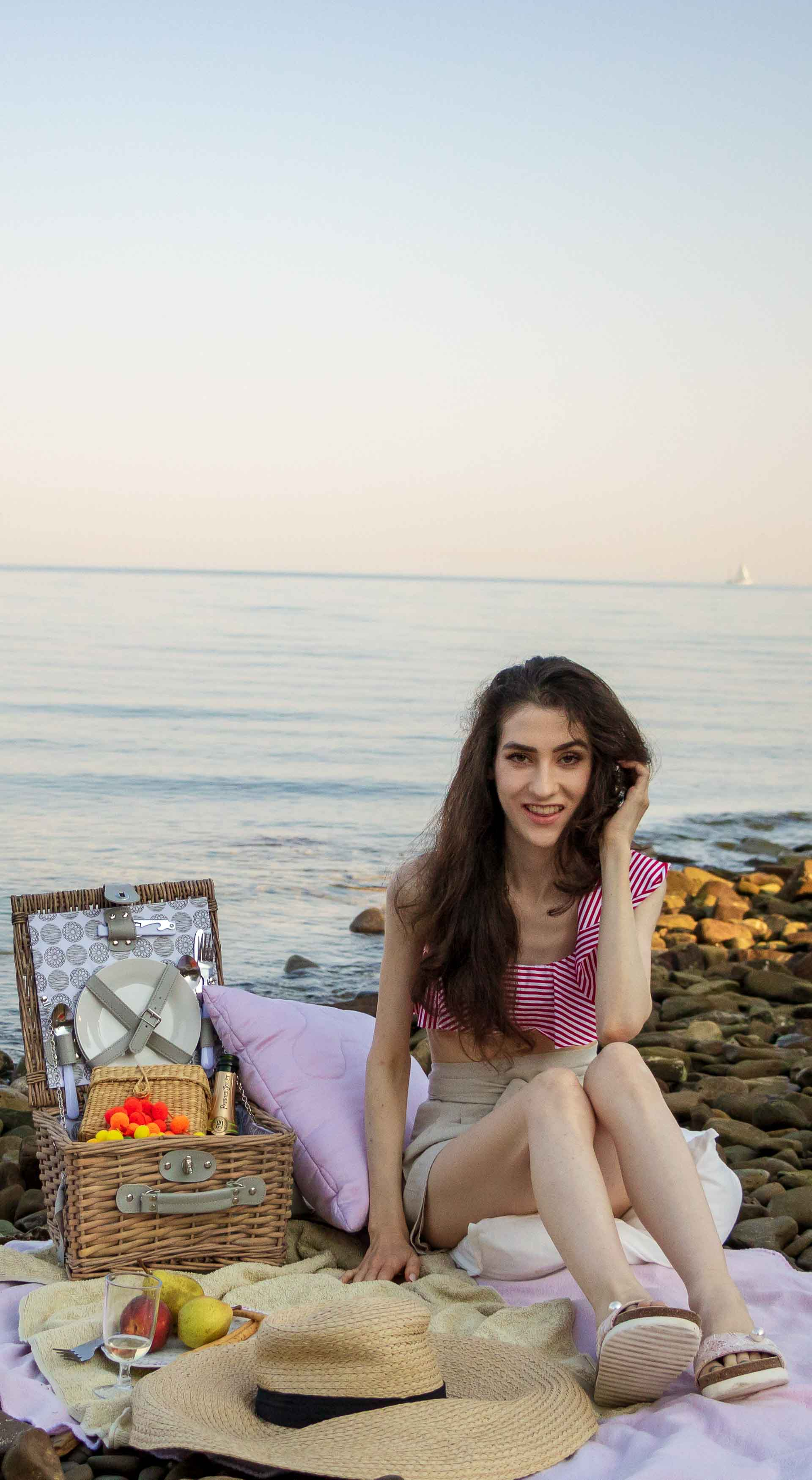 Slovenian Fashion Blogger Veronika Lipar of Brunette from Wall wearing Calzedonia red striped bikini top, paper bag linen shorts, luxe pool slides, large straw hat, Nannacay basket bag while sitting on a picnic blanket, having picnic on the beach