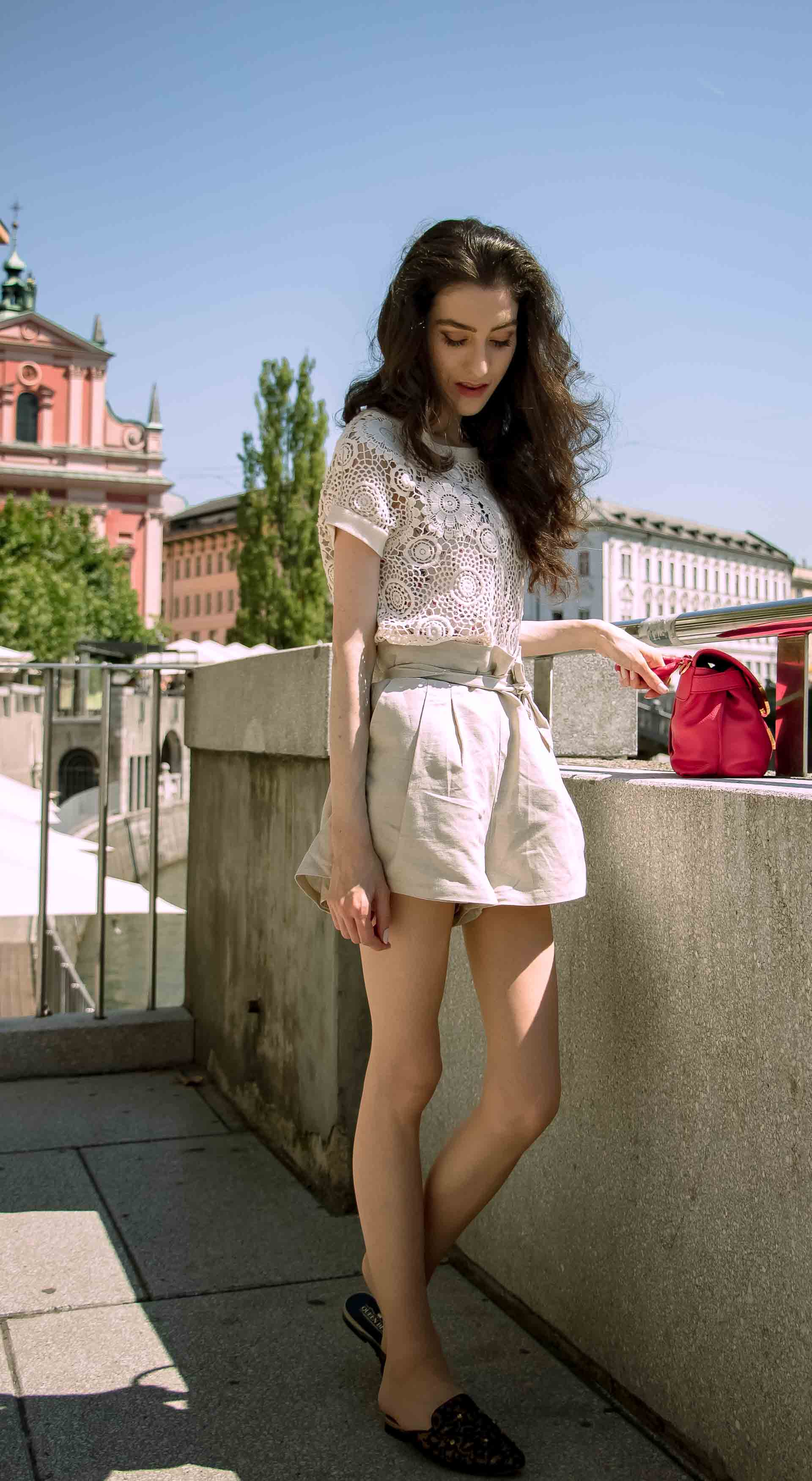 Beautiful Slovenian Fashion Blogger Veronika Lipar of Brunette from Wall wearing beige linen shorts, crochet top, black slip-ons shoes, pink top handle bag, standing on the street in Ljubljana