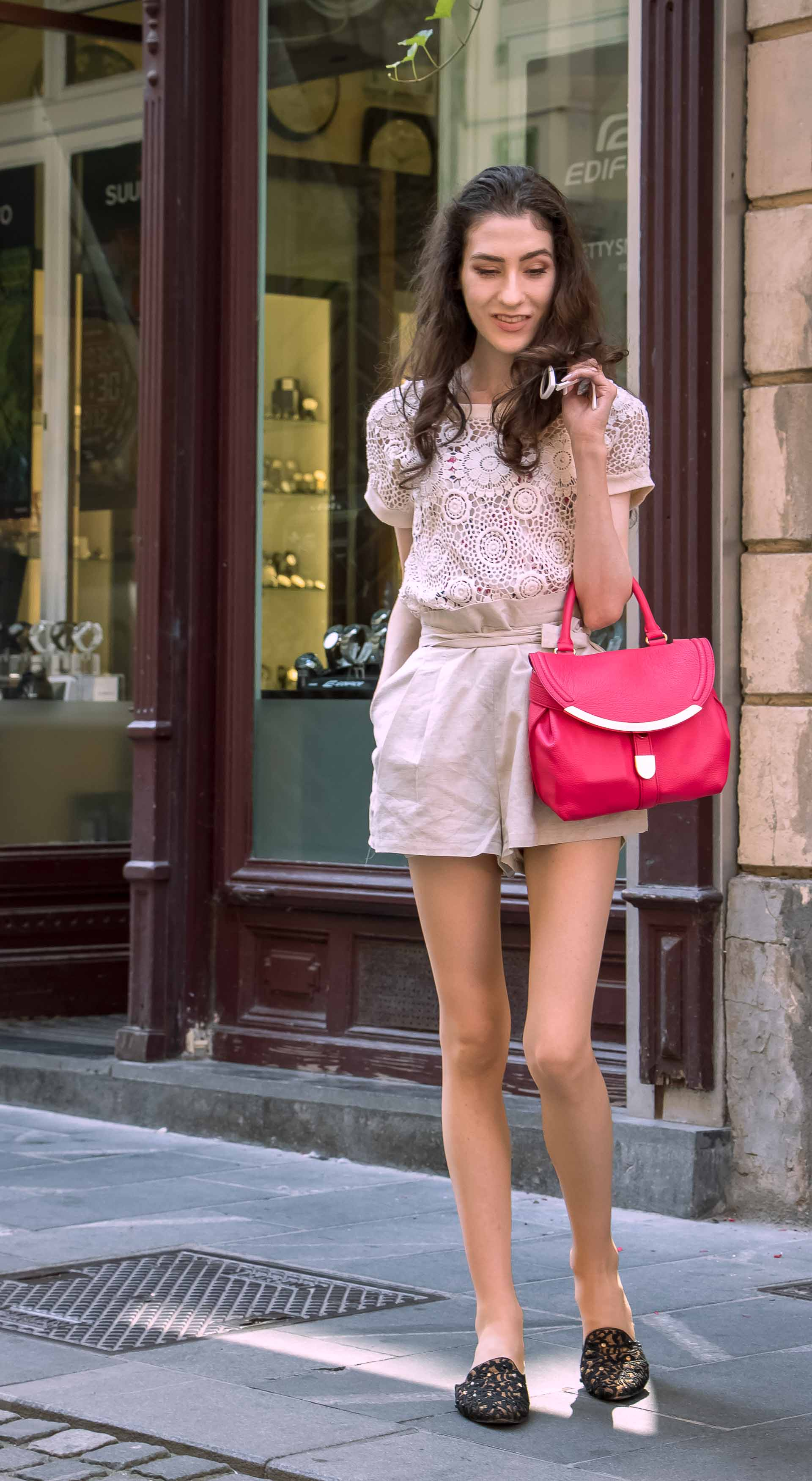Beautiful Slovenian Fashion Blogger Veronika Lipar of Brunette from Wall wearing beige linen shorts, crochet top, black slip-ons shoes, pink top handle bag, standing infant of the store front