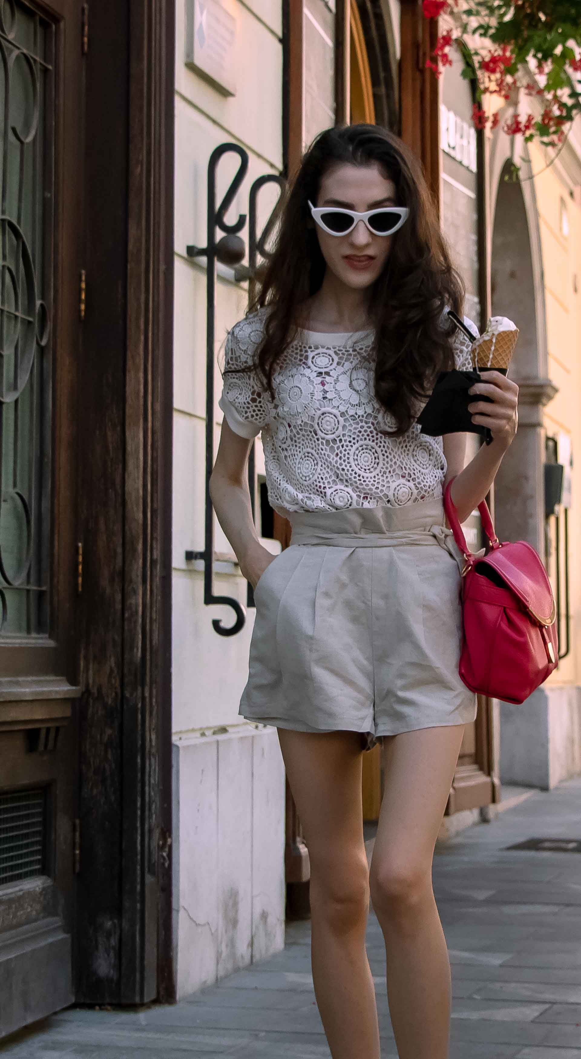 Beautiful Slovenian Fashion Blogger Veronika Lipar of Brunette from Wall wearing beige linen shorts, crochet top, black slip-ons shoes, pink top handle bag, holding ice cream in a cone while walking down the street