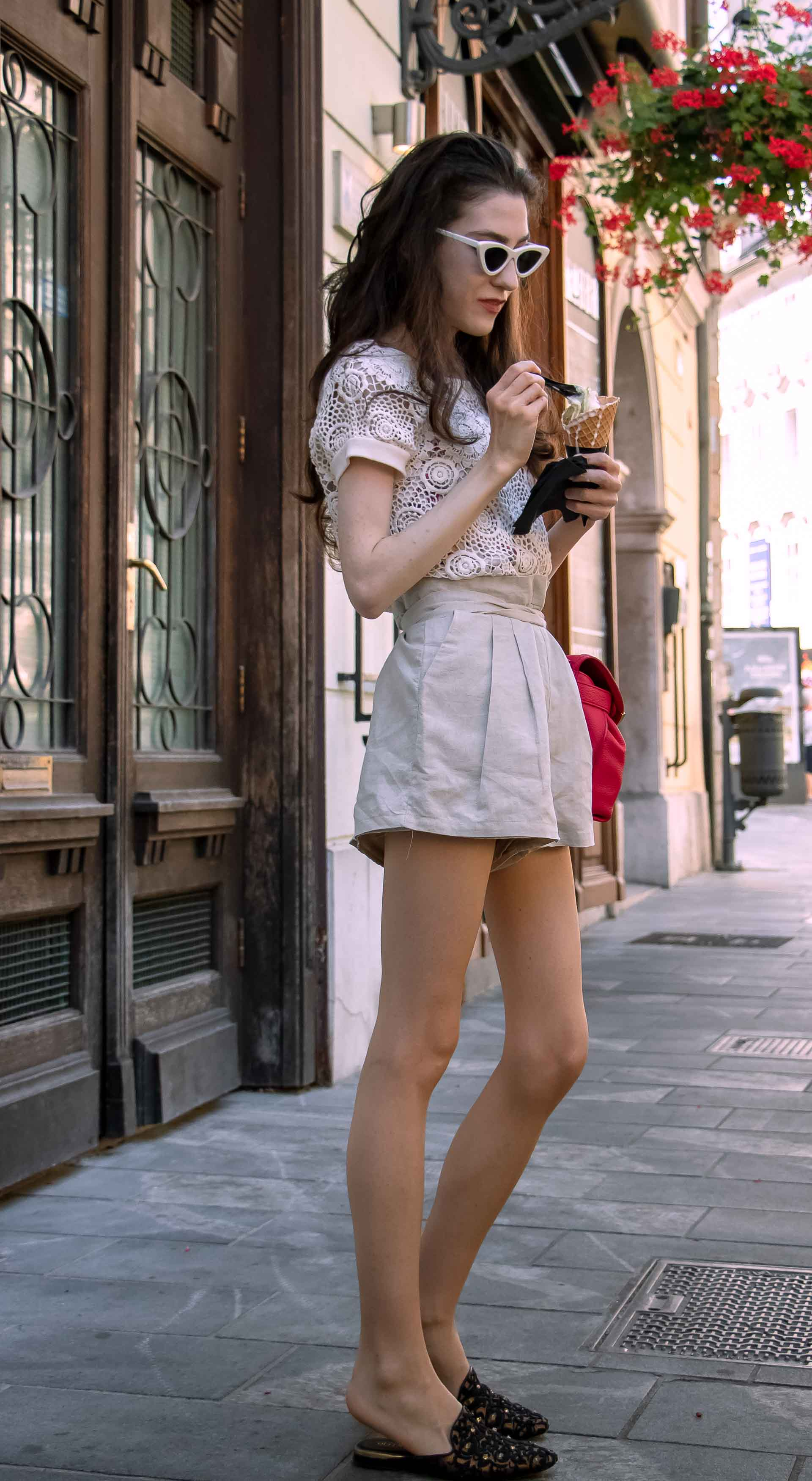 Beautiful Slovenian Fashion Blogger Veronika Lipar of Brunette from Wall wearing beige linen shorts, crochet top, black slip-ons shoes, pink top handle bag, eating ice cream in a cone while walking down the street