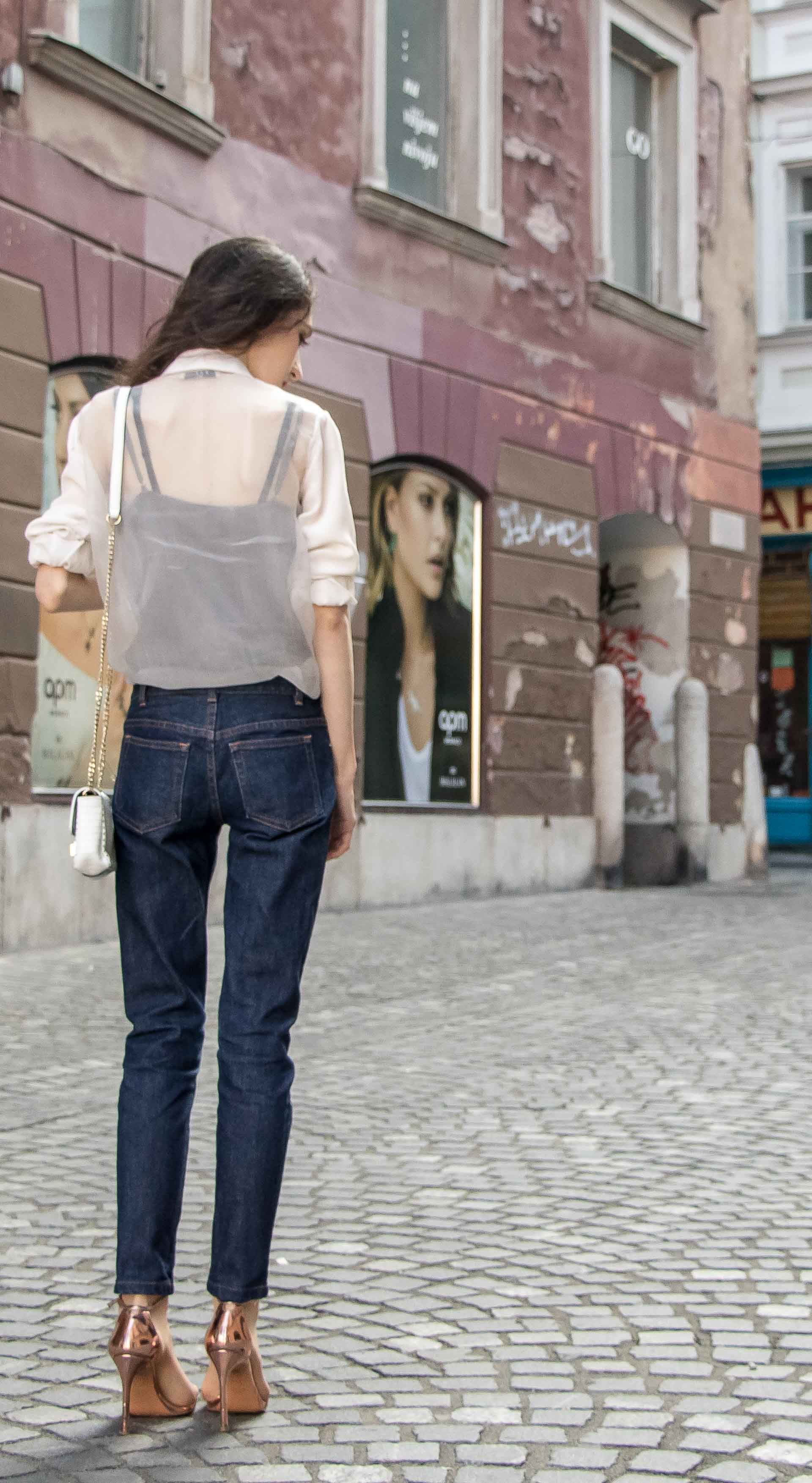Beautiful Slovenian Fashion Blogger Veronika Lipar of Brunette from Wall wearing chic outfit, white silk shirt from Sandro Paris, A.P.C. straight-leg dark denim jeans, Stuart Weitzman Nudistsong metallic sandals, chain shoulder bag showing back