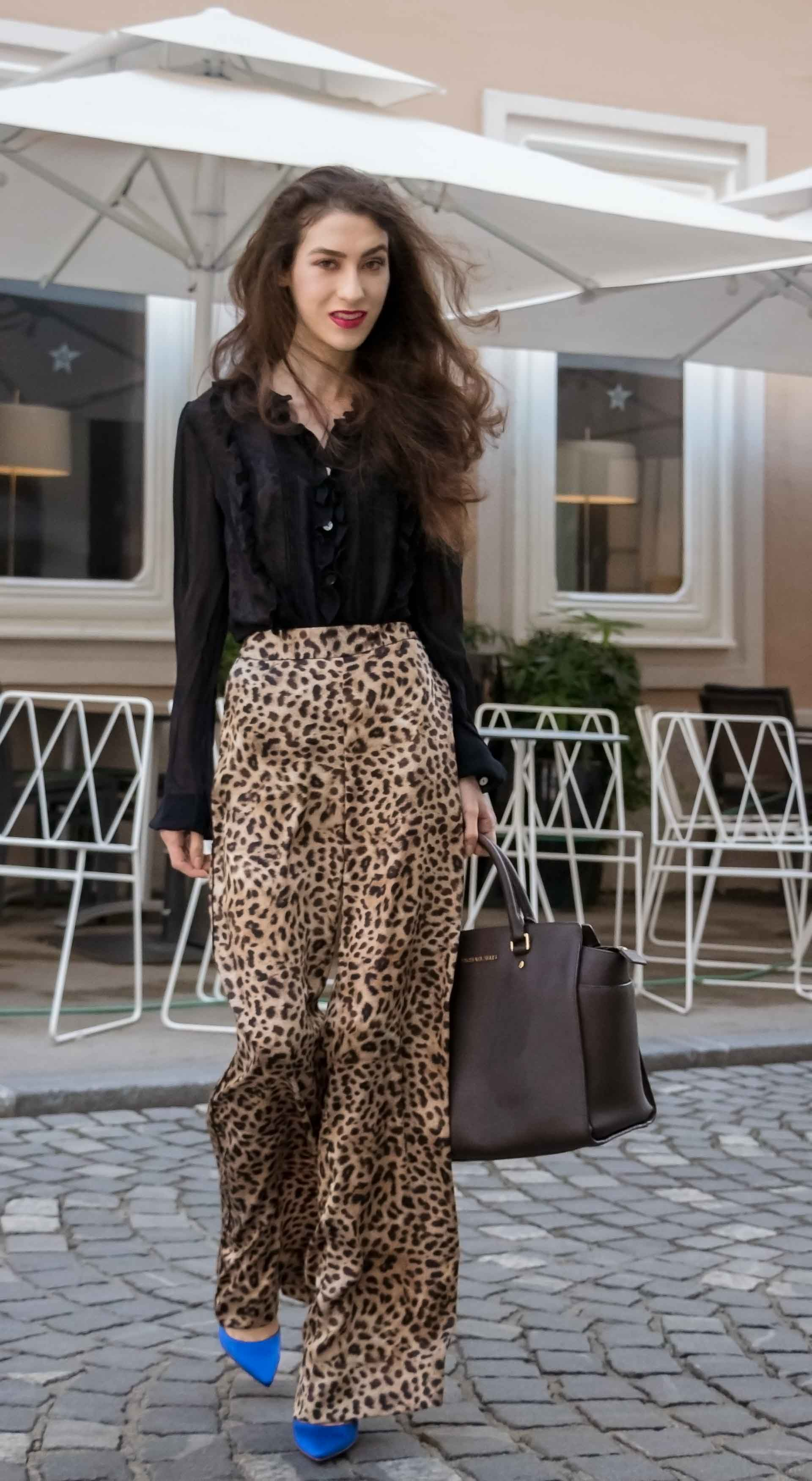 Beautiful Slovenian Fashion Blogger Veronika Lipar of Brunette from Wall wearing Tom Ford Liquid Metal Lip Lacquer, black sheer blouse, Zara leopard print wide-leg pants, blue Gianvito Rossi satin pumps, brown Michael Kors Selma tote bag, walking on the street in Ljubljana