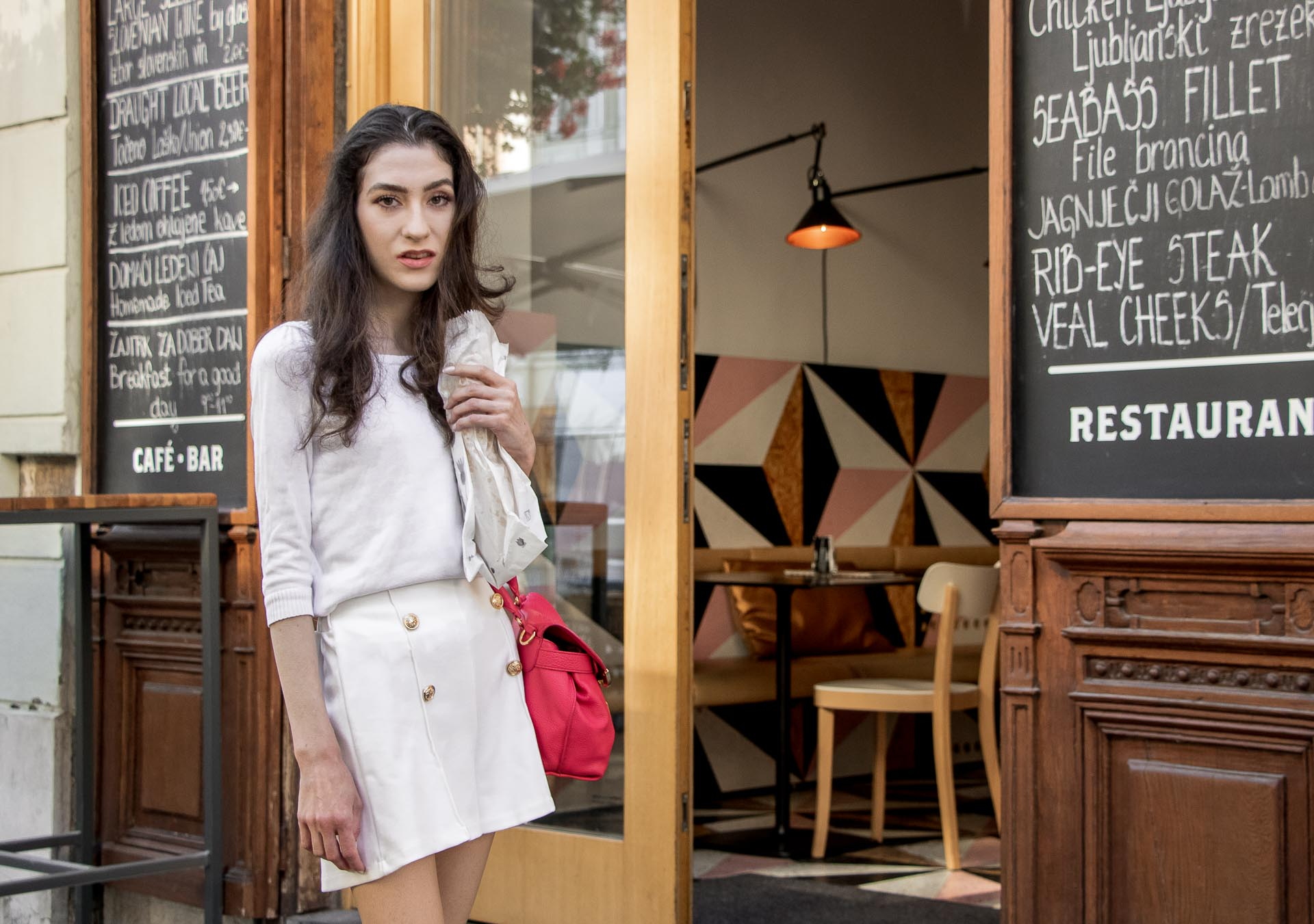 Slovenska modna blogerka Veronika Lipar of Brunette from Wall wearing all in white outfit, a white sweater, white tailored shorts, pink top handle bag, a paper bag on the street in Ljubljana