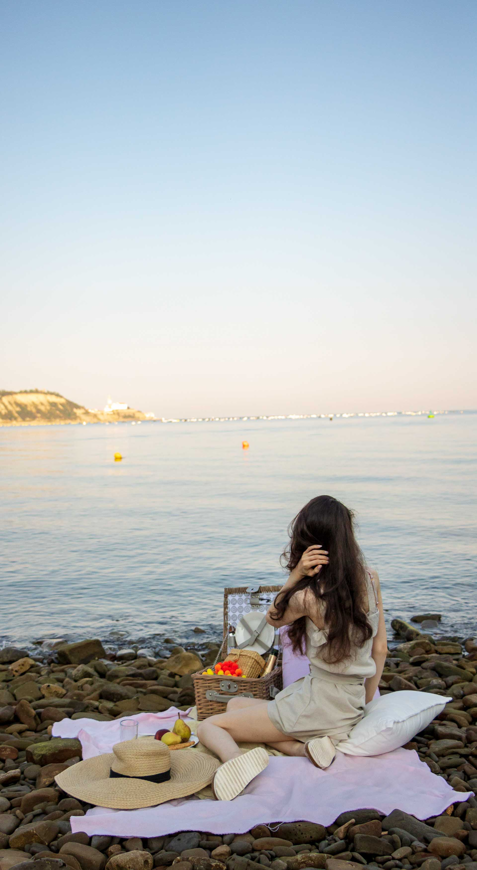 Slovenian Fashion Blogger Veronika Lipar of Brunette from Wall wearing beige linen crop top, paper bag linen shorts, luxe pool slides, large straw hat, Nannacay basket bag while sitting on a picnic blanket and watching the sea