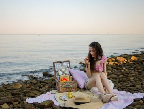 Slovenian Fashion Blogger Veronika Lipar of Brunette from Wall wearing beige linen crop top, paper bag linen shorts, luxe pool slides, large straw hat, Nannacay basket bag while having picnic on the beach