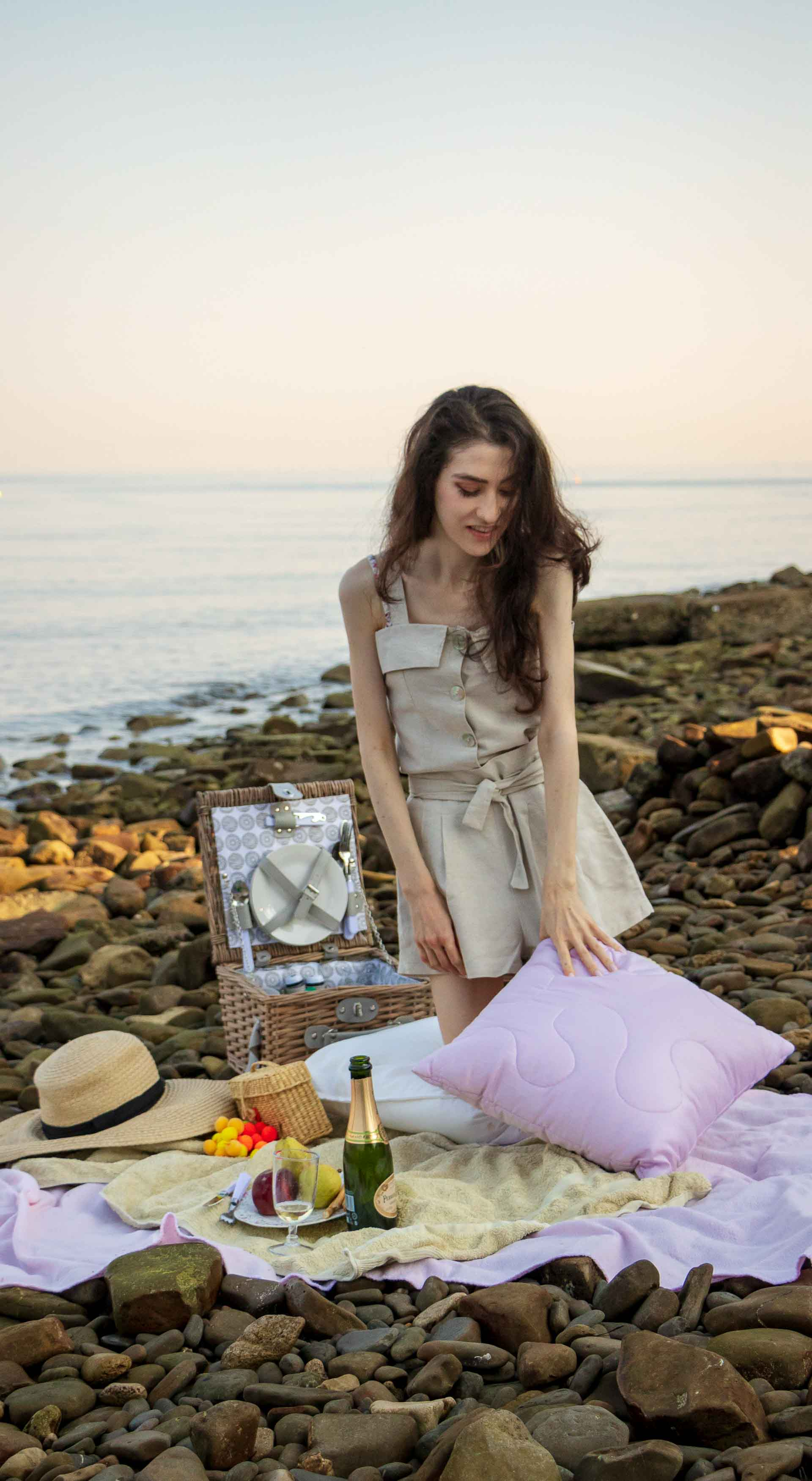 Slovenian Fashion Blogger Veronika Lipar of Brunette from Wall dressed in beige linen crop top, paper bag linen shorts, luxe pool slides, large straw hat, Nannacay basket bag while playing with pillows at beach picnic