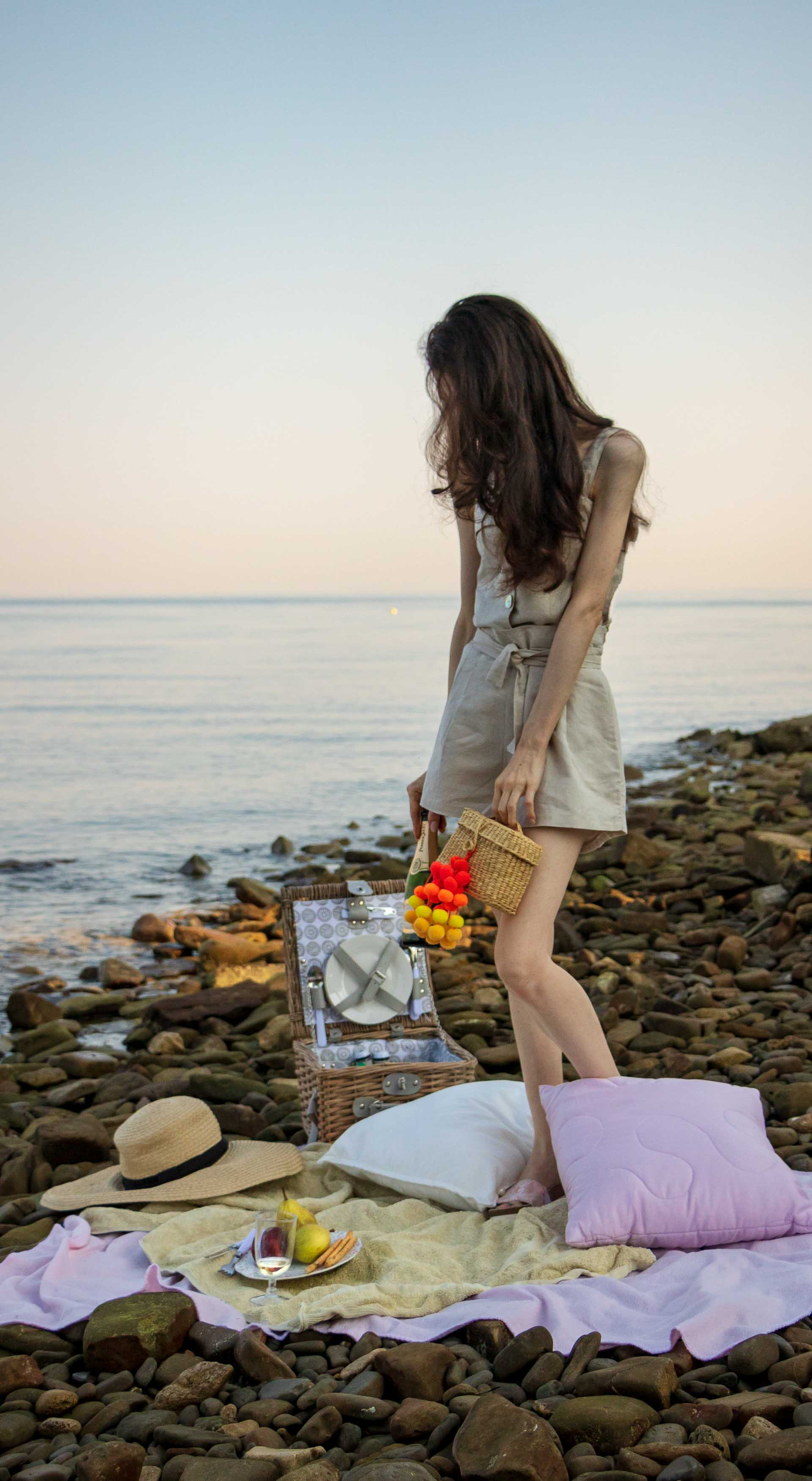 Slovenian Fashion Blogger Veronika Lipar of Brunette from Wall dressed in beige linen crop top, paper bag linen shorts, luxe pool slides, large straw hat, Nannacay basket bag while having picnic on the beach