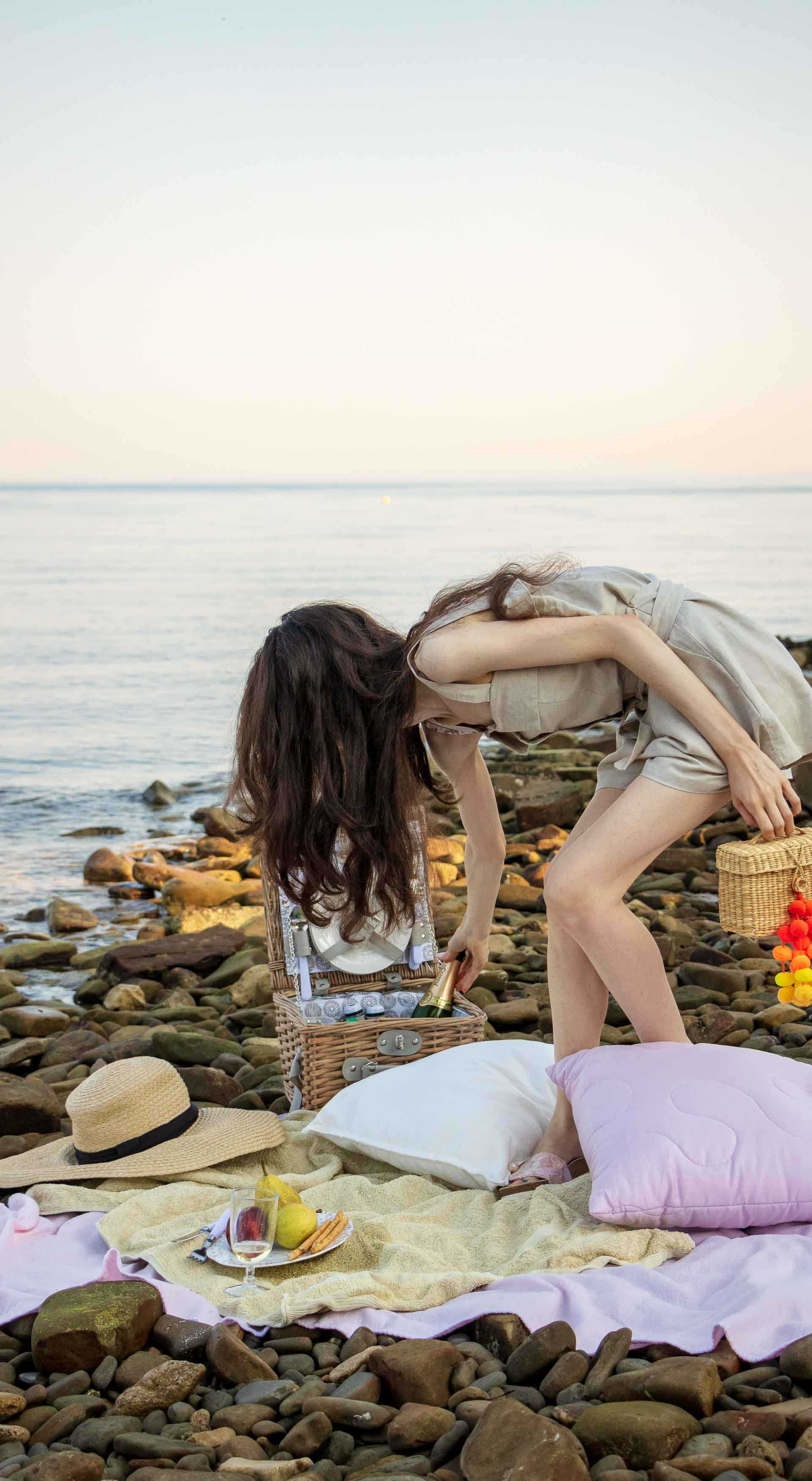 Slovenian Fashion Blogger Veronika Lipar of Brunette from Wall dressed in beige linen crop top, paper bag linen shorts, luxe pool slides, large straw hat, Nannacay basket bag while preparing beach picnic