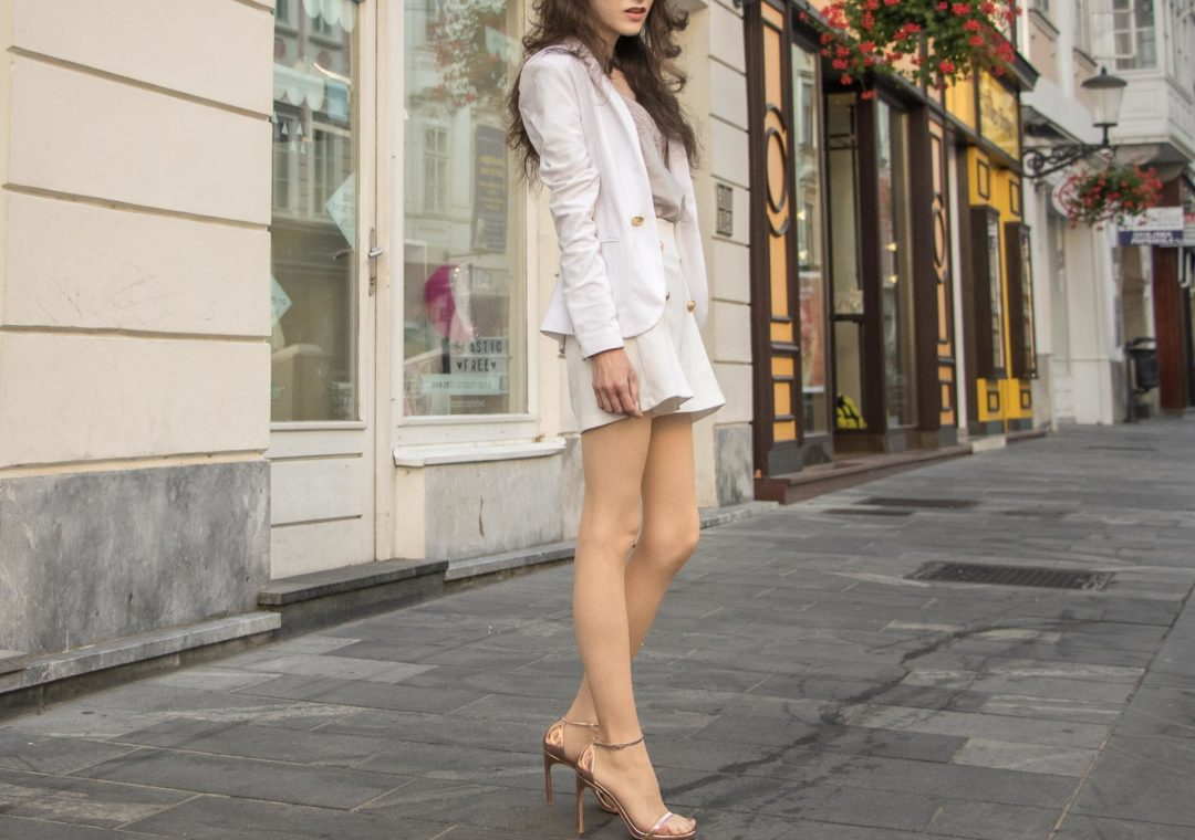 Slovenian Fashion Blogger Veronika Lipar of Brunette from Wall wearing white short suit, white blazer, white button front shorts, Stuart Weitzman nudist song metallic sandals, white chain shoulder bag for a civil summer wedding