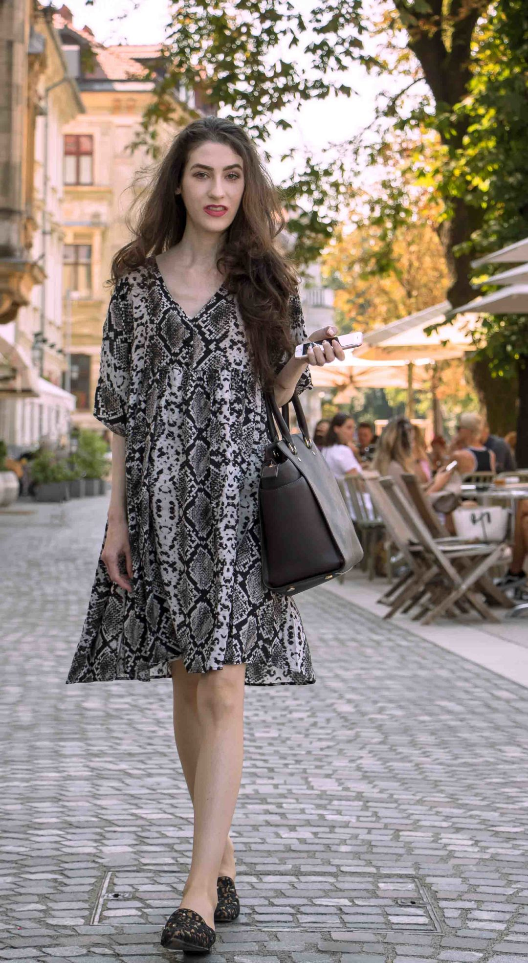 Beautiful Slovenian Fashion Blogger Veronika Lipar of Brunette from Wall dressed in flowing short snake print dress from Zara, black flat mules walking on the street in Ljubljana